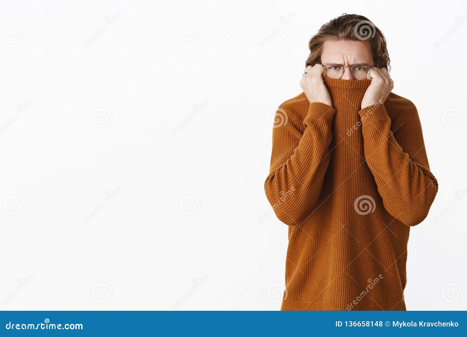 Studioschot van ontstemde gehinderde leuke Kaukasische kerel met lang eerlijk haar en glazen teleurgesteld fronsen zoals schudden