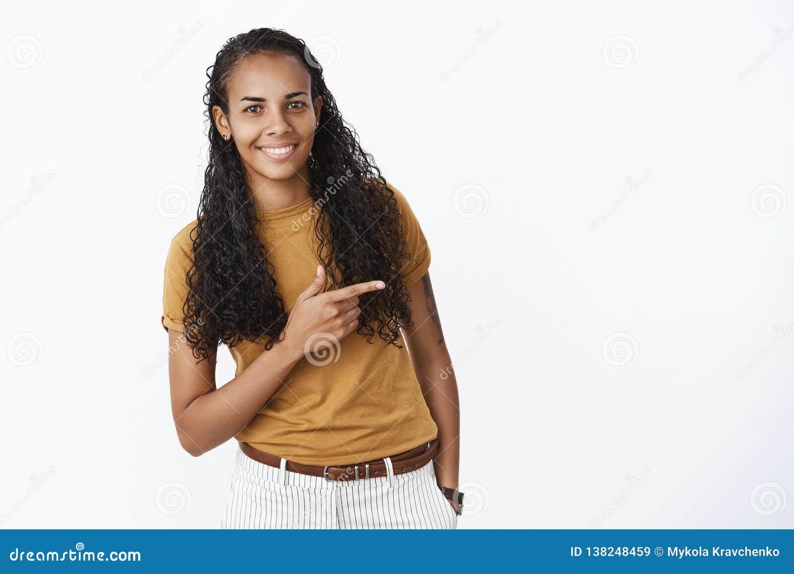 Studioschot van schuwe en leuke vrij jonge Afrikaanse Amerikaanse vrouw met lang krullend haar die zoals net richtend met buigen