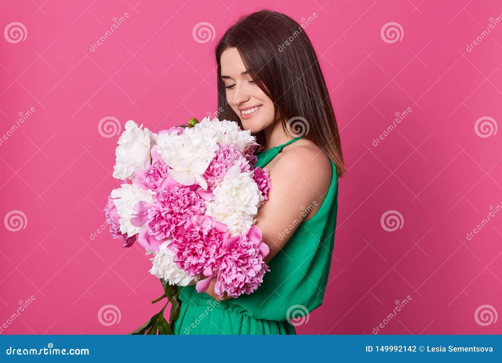 Studioskott av den härliga brunettflickan som omfamnar den stora buketten med rosa och vita pioner, stilfull charmig dam som pose
