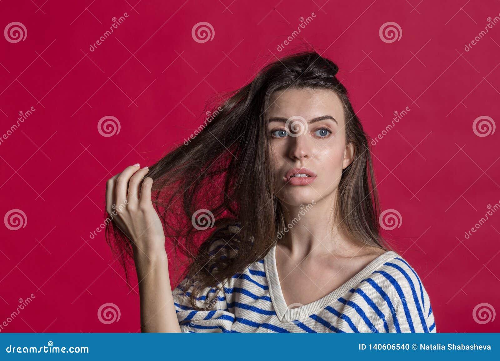 Studioskott av en älskvärd härlig kvinna som isoleras mot en tom röd studiovägg