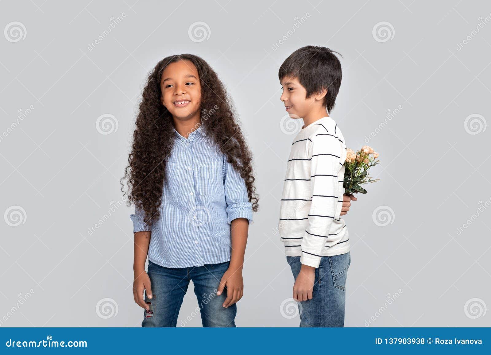 Studioskott av en ung pojke som ger blommor till en flicka som isoleras