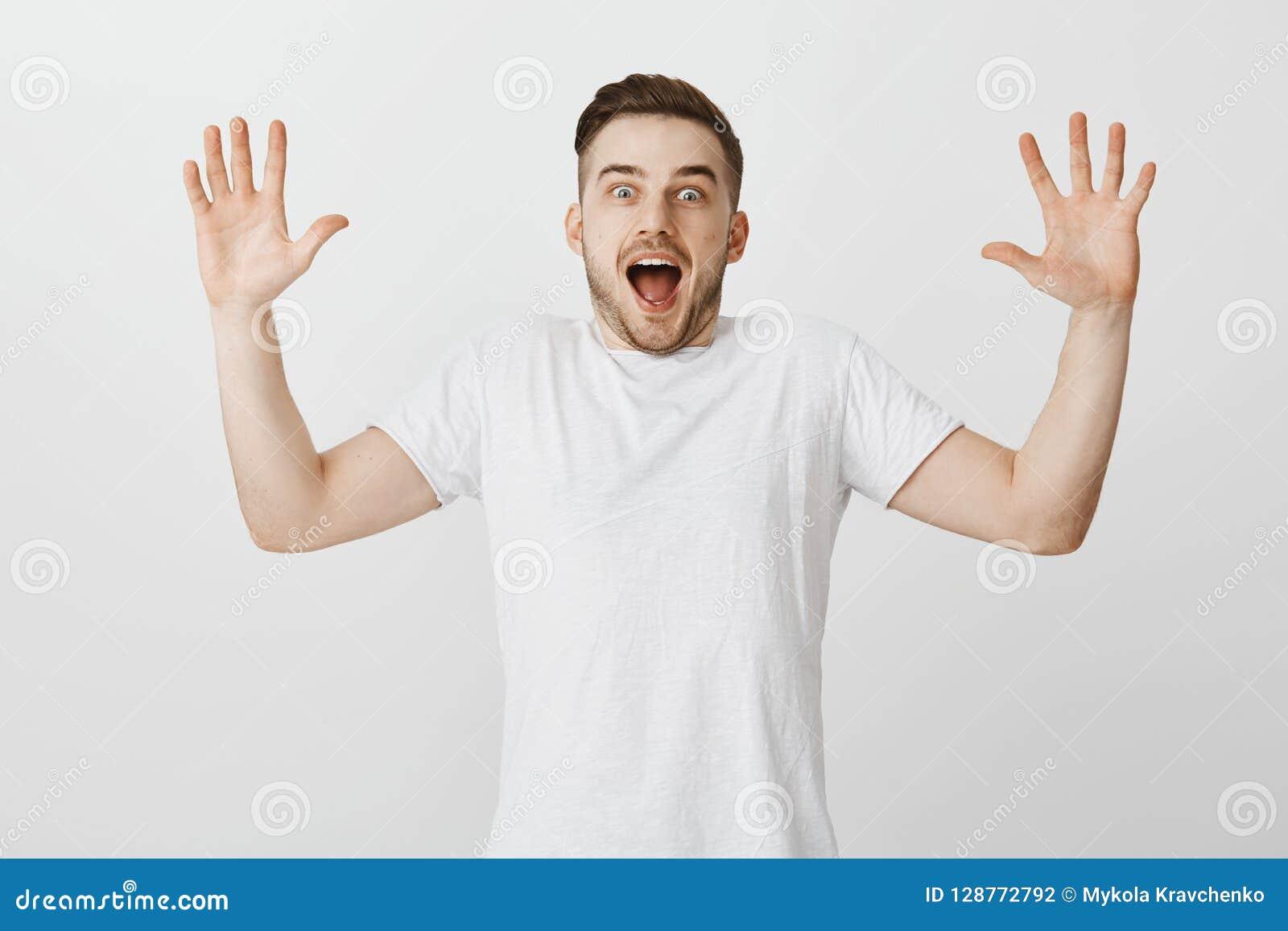 Studioskottet av den upphetsade entusiastiska stiliga mannen med att lyfta för borst gömma i handflatan höjd och att ropa från ly