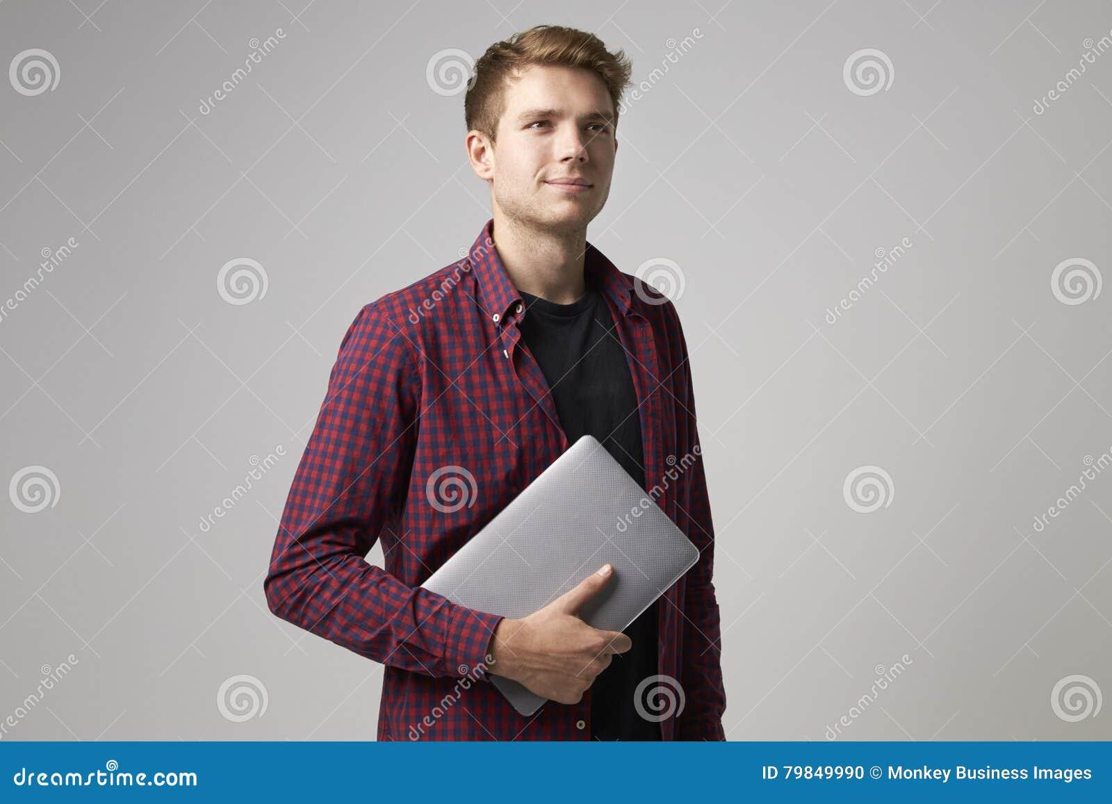 Studiostående av den tillfälligt klädda affärsmannen With Laptop
