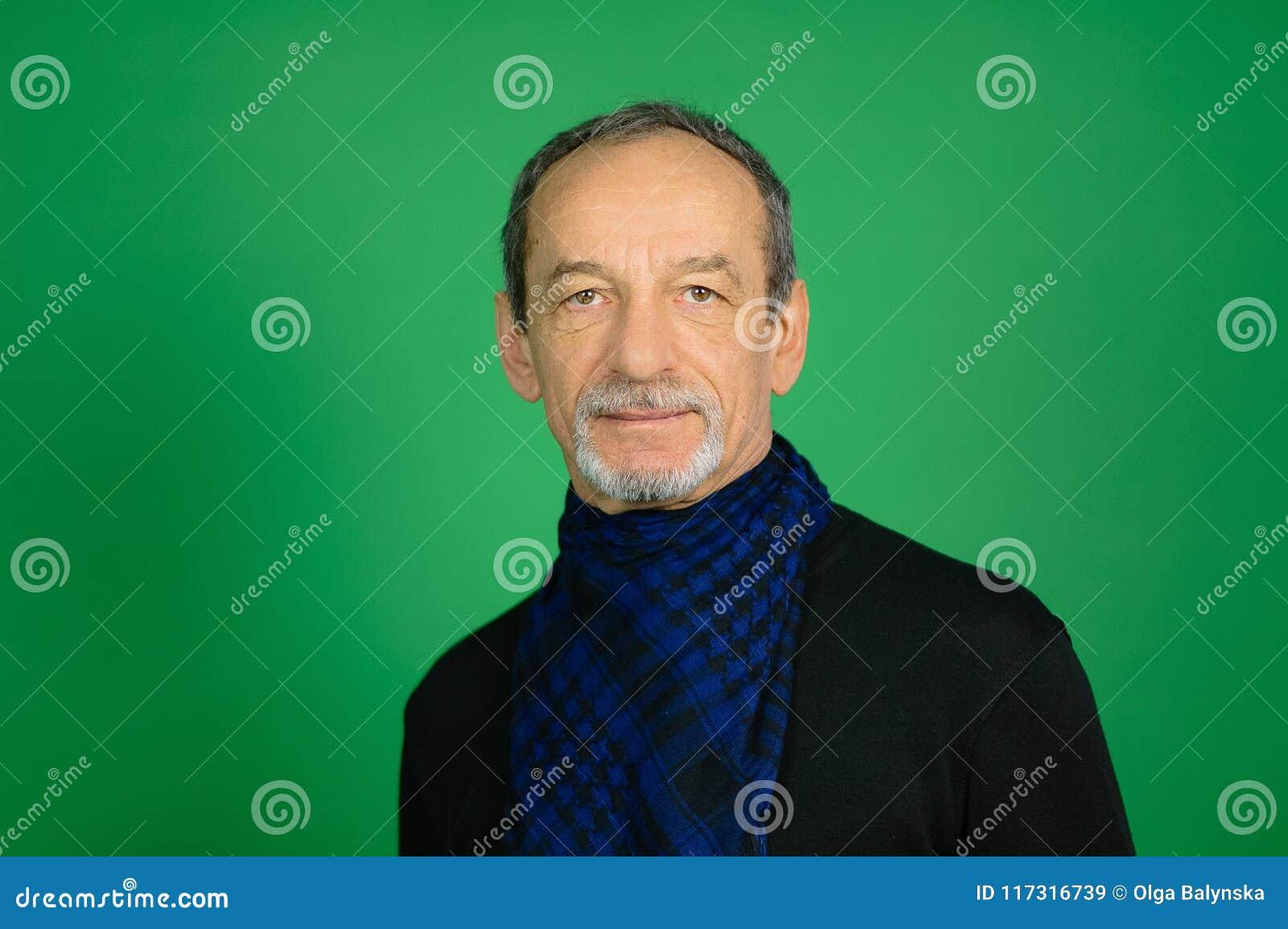 Studiostående av en hög gråhårig man med detklippte skägget i svart tröja och blå rutig halsduk runt om hans