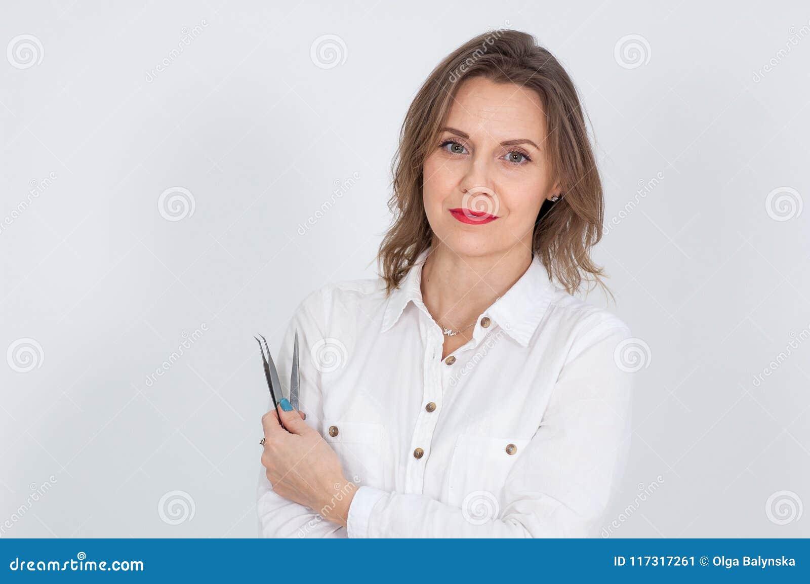 Studiostående av för Visagist för attraktiv kvinnlig pincett hållande ögonbryn på hennes händer och att se kameran på vit