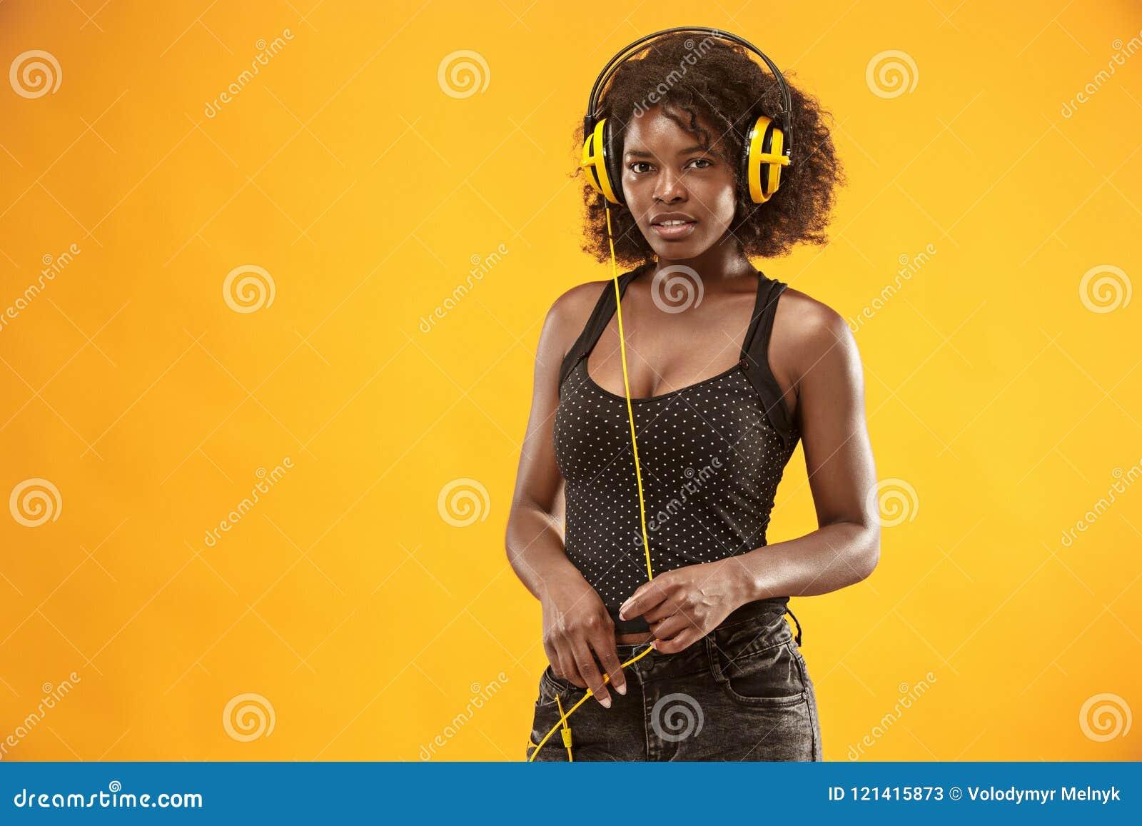 Studiostående av lyckligt le för förtjusande lockig flicka under photoshoot Bedöva den afrikanska kvinnan med ljus-brunt hud