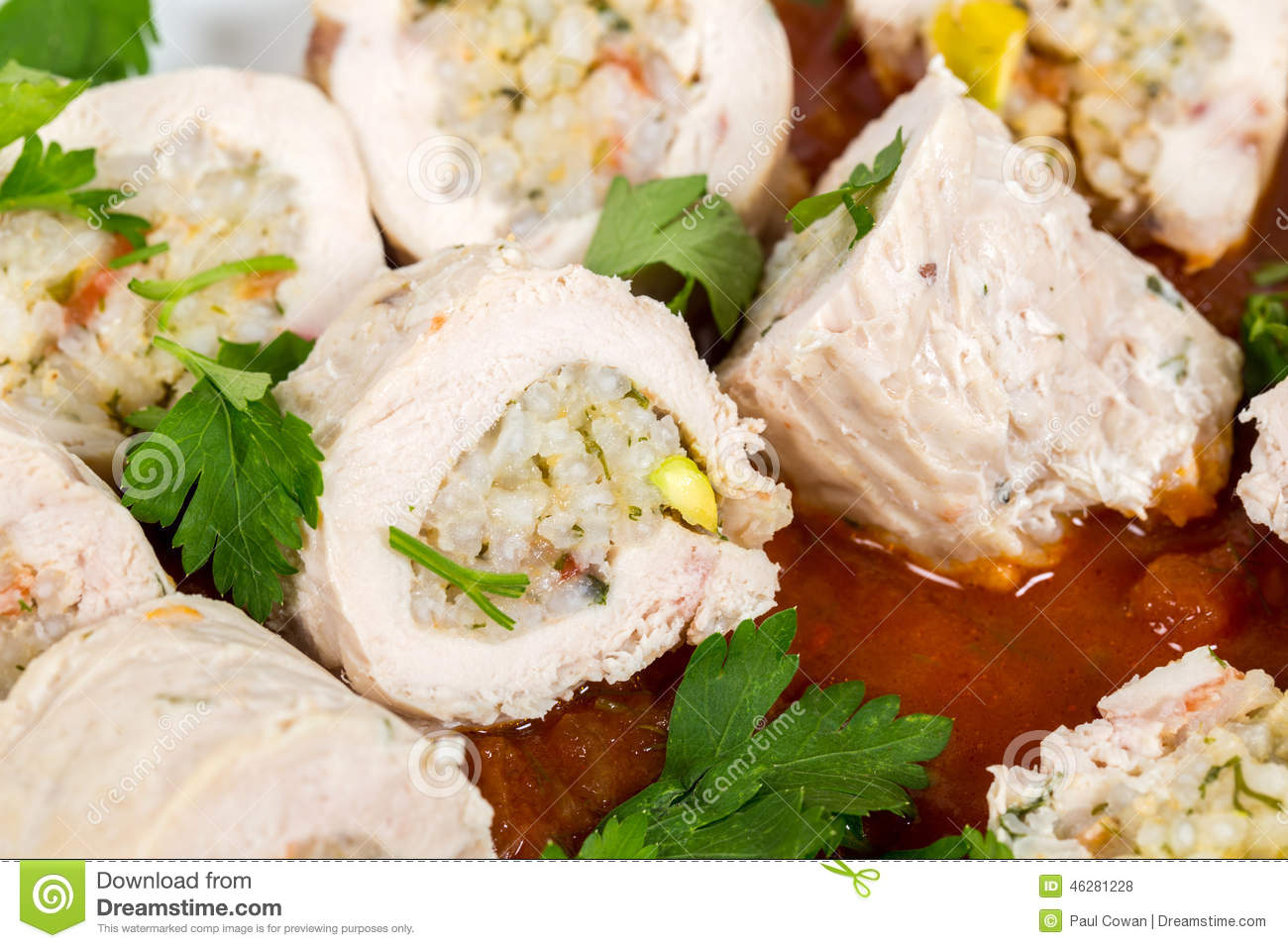 Chicken breasts stuffed with rice, herbs, tomato and pistachios served ...