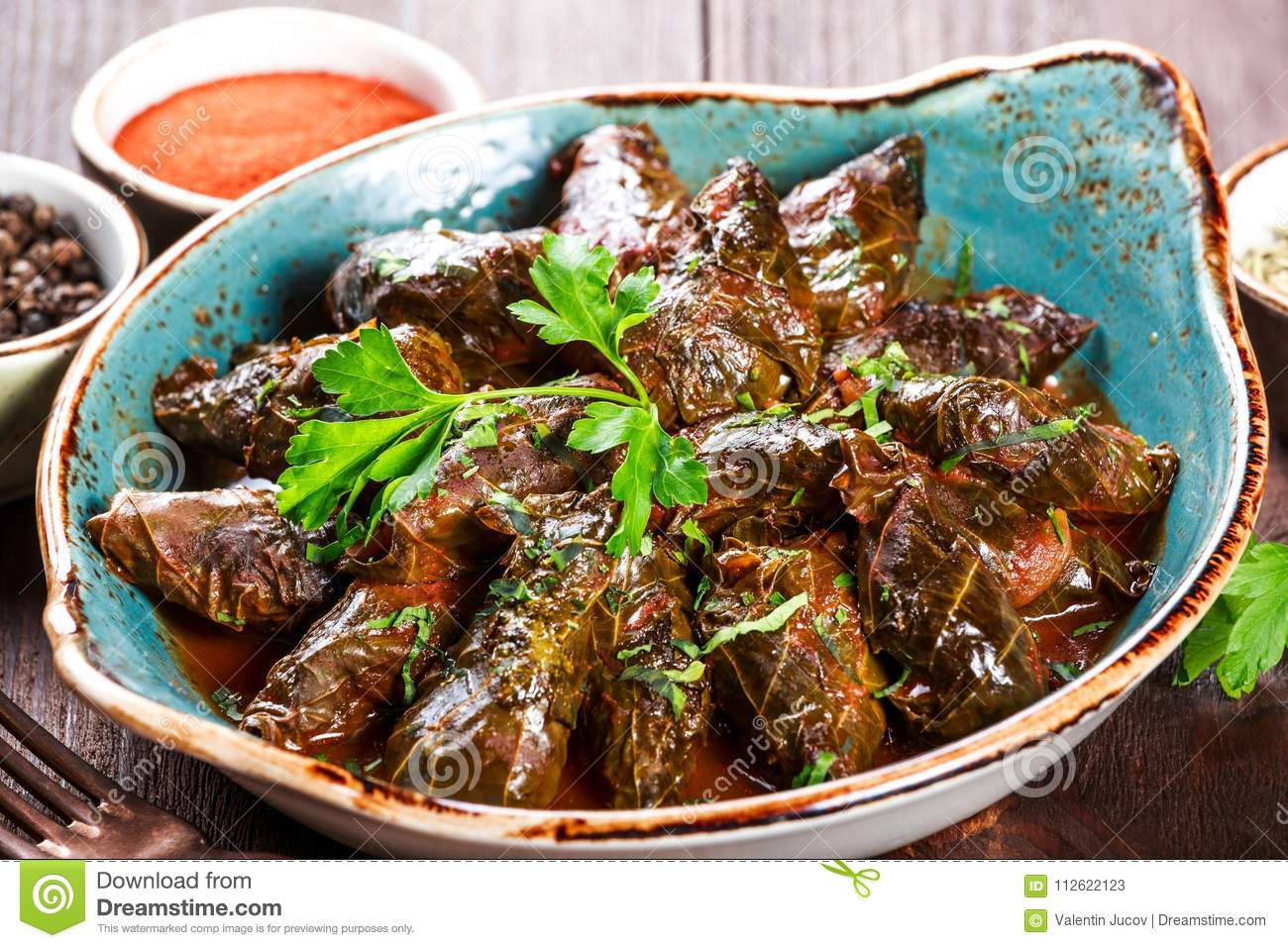 Stuffed grape leaves with rice and herbs on plate on wooden background - Dolma, tolma, sarma.