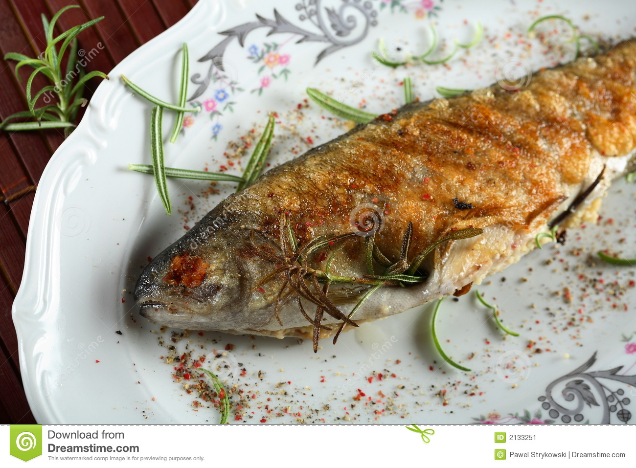 Stuffed grilled trout in the breadcrumbs decorated with herbs.