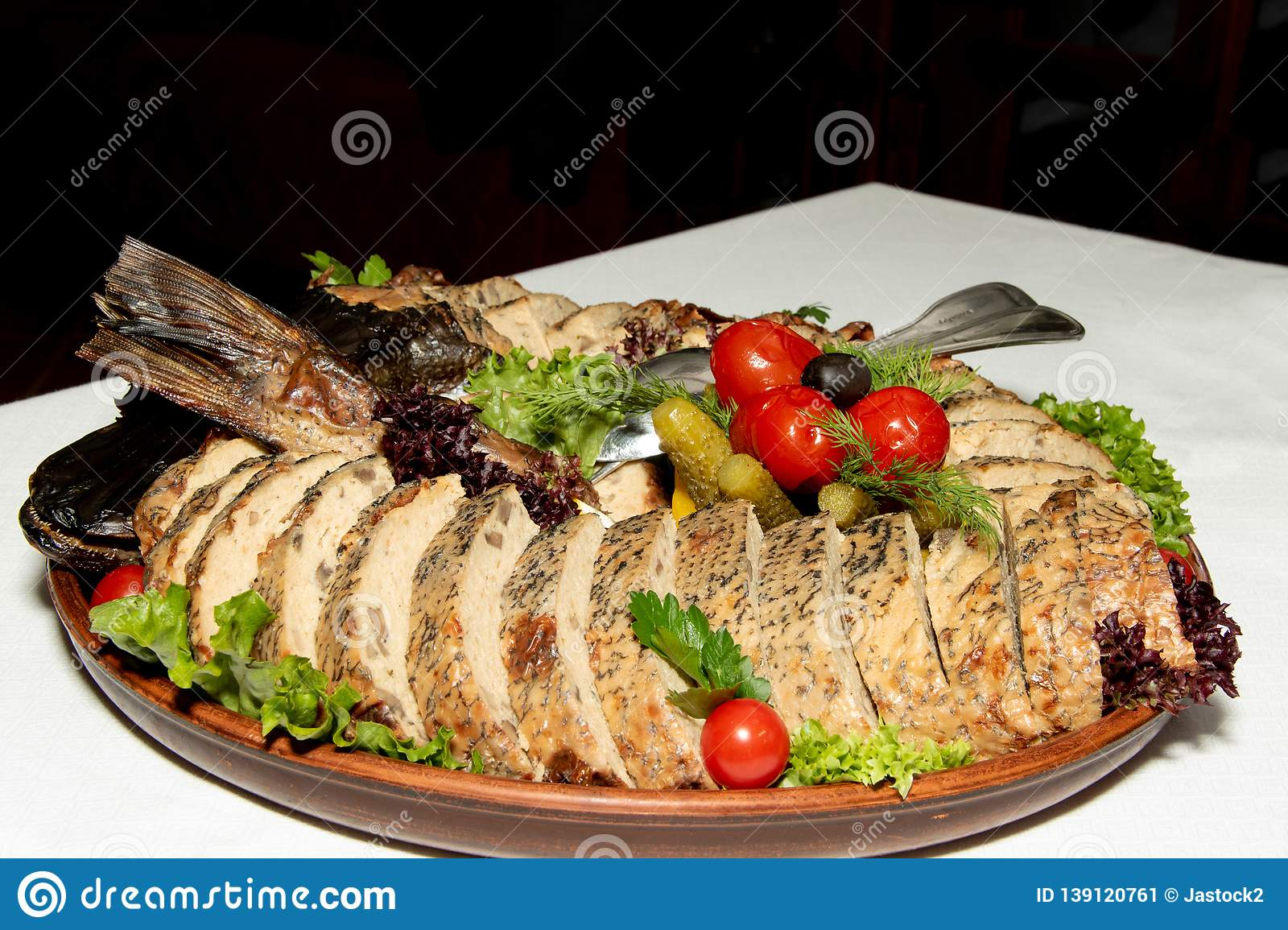 Stuffed pike on a plate of vegetables and leaves of green salad