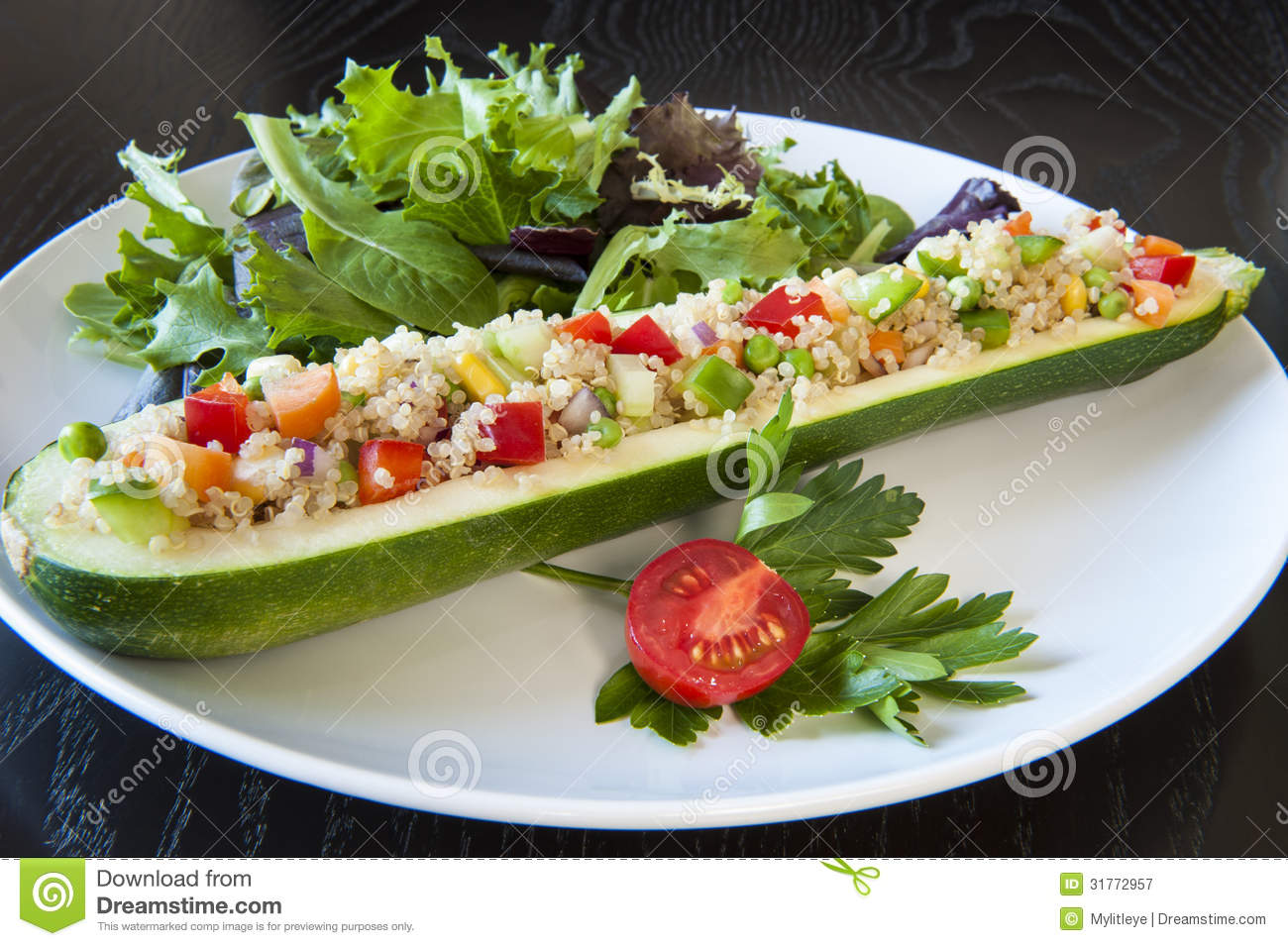 Zucchini stuffed with quinoa and vegetables on a white plate.