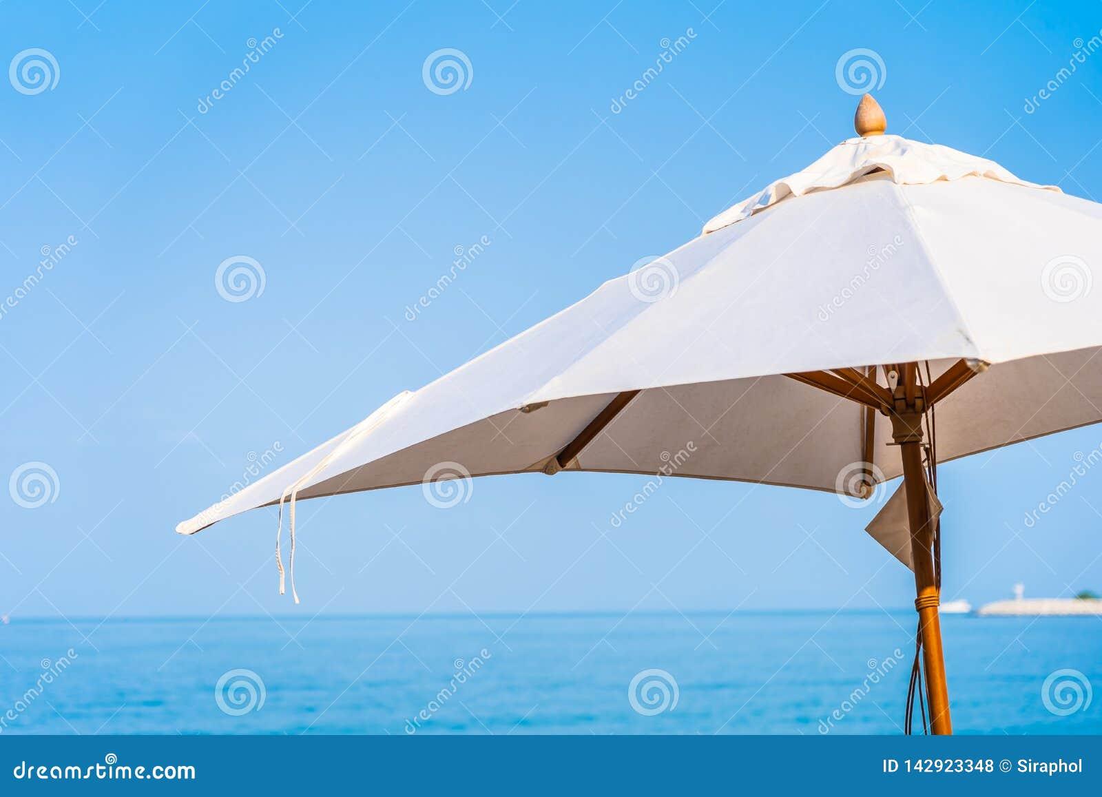 Stuhlregenschirm und -aufenthaltsraum auf dem schönen Strandseeozean auf Himmel