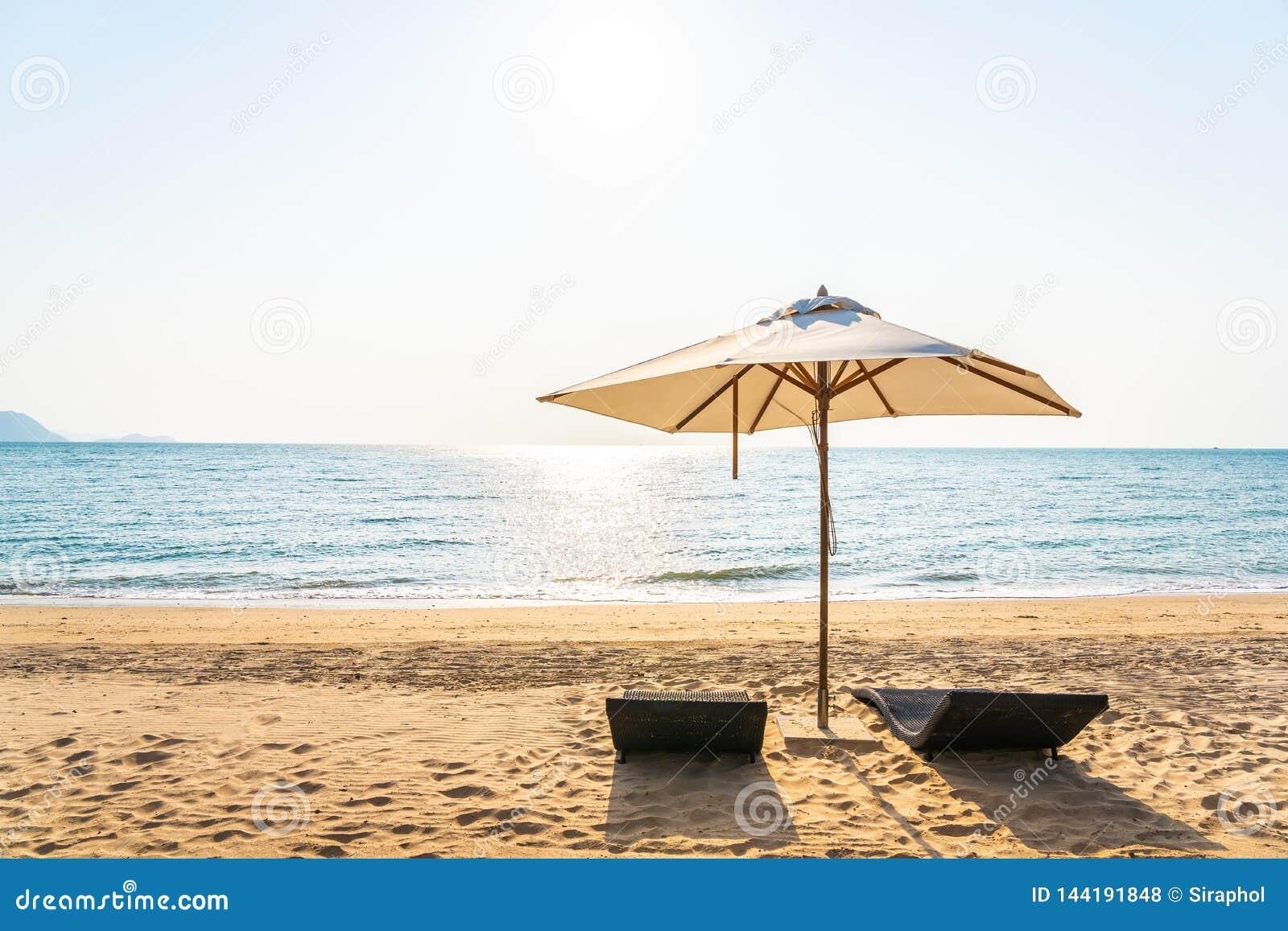 Stuhlregenschirm und -aufenthaltsraum auf dem sch?nen Strandseeozean auf Himmel