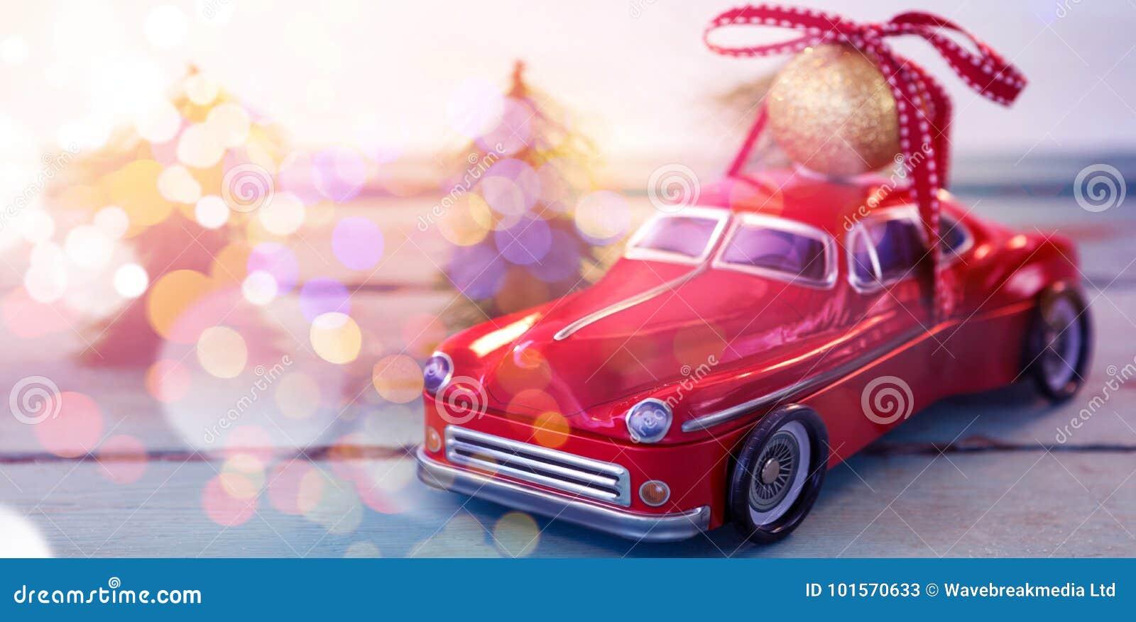 Stuk speelgoed de snuisterijbal van auto dragende Kerstmis op houten plank