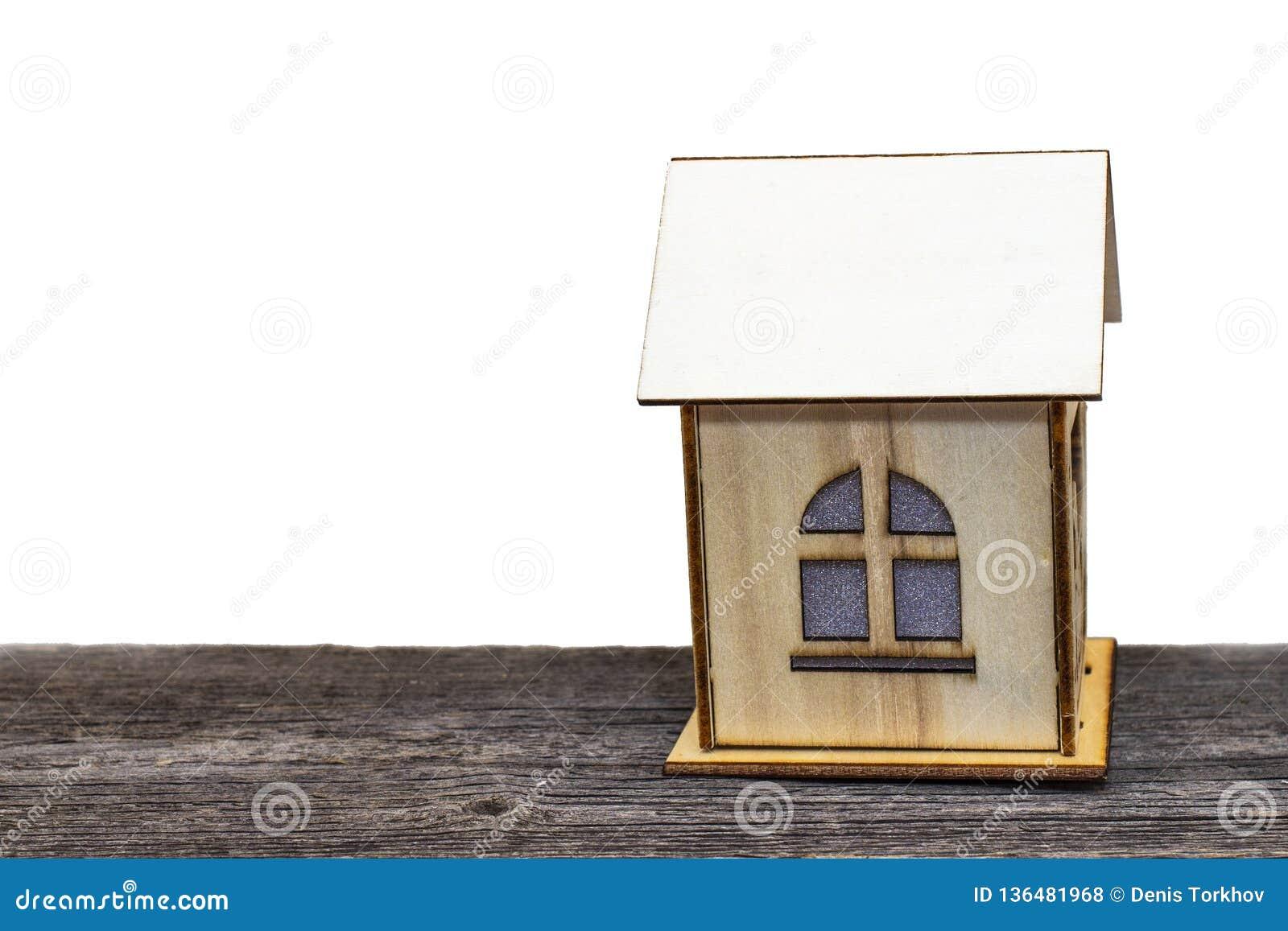 Stuk speelgoed huis met sleutels en contant geld op oude houten Raad, op wit geïsoleerde achtergrond