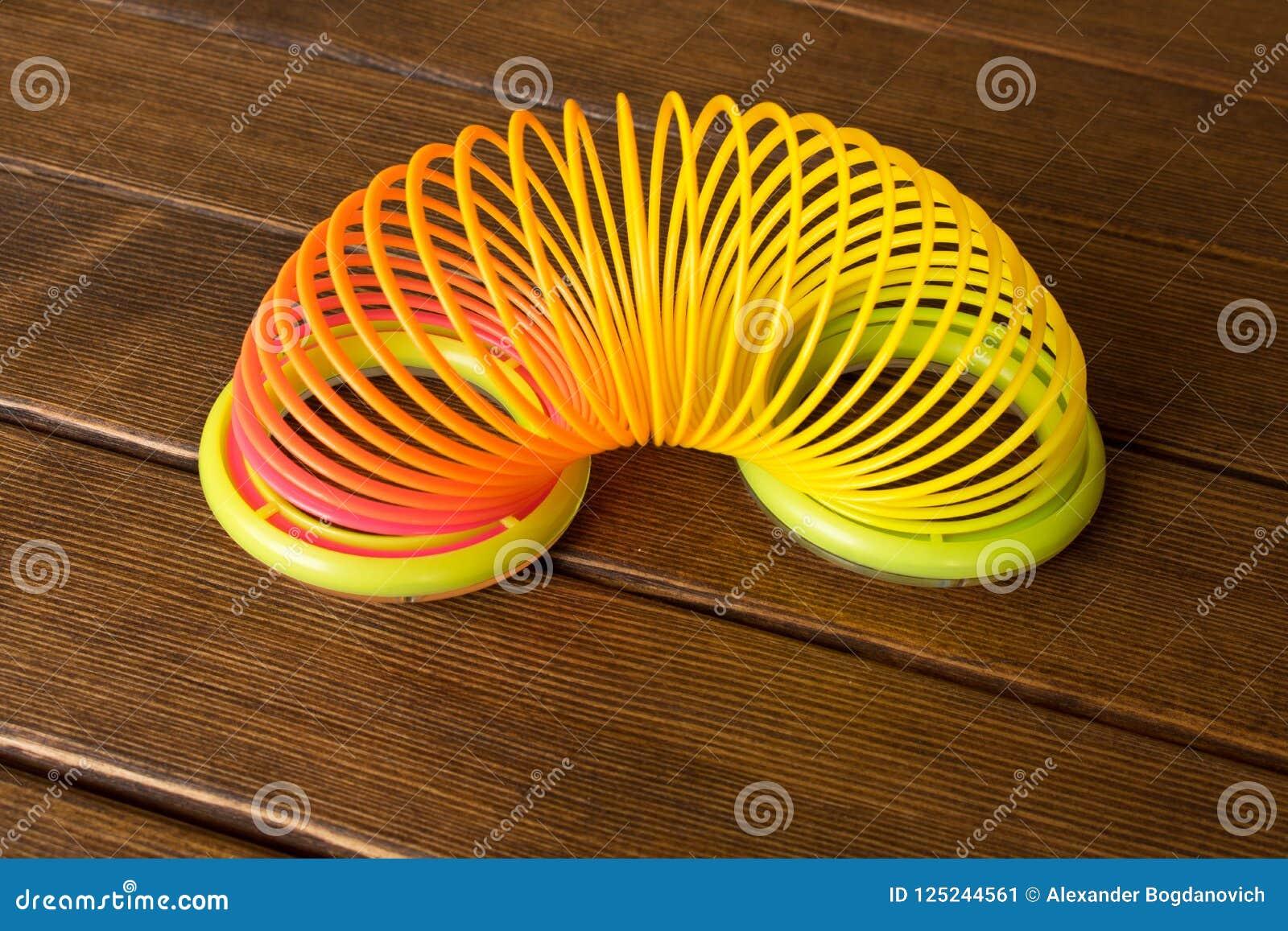 Stuk speelgoed plastic regenboog op een houten lijst Multi-colored spiraal voor