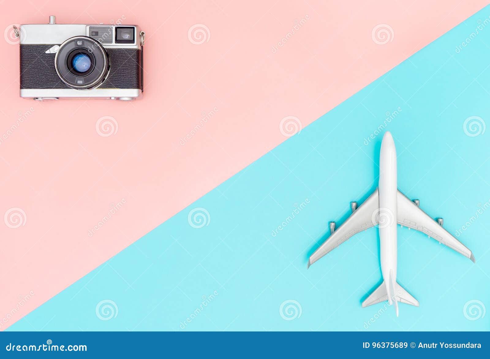 Stuk speelgoed vliegtuig en camera op roze en blauwe achtergrond