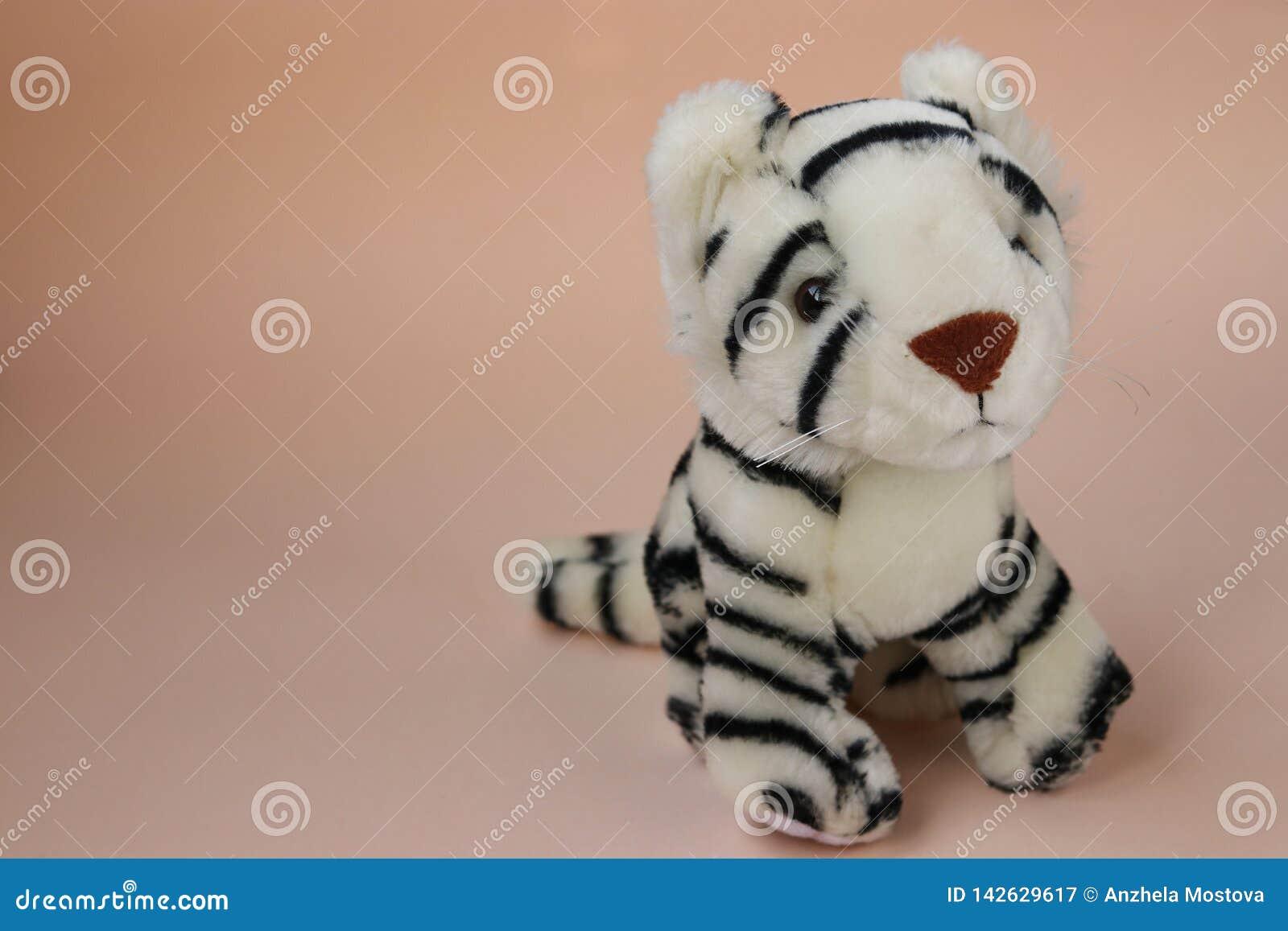 Stuk speelgoed witte tijgerwelp op perzikachtergrond met bezinning van schaduw