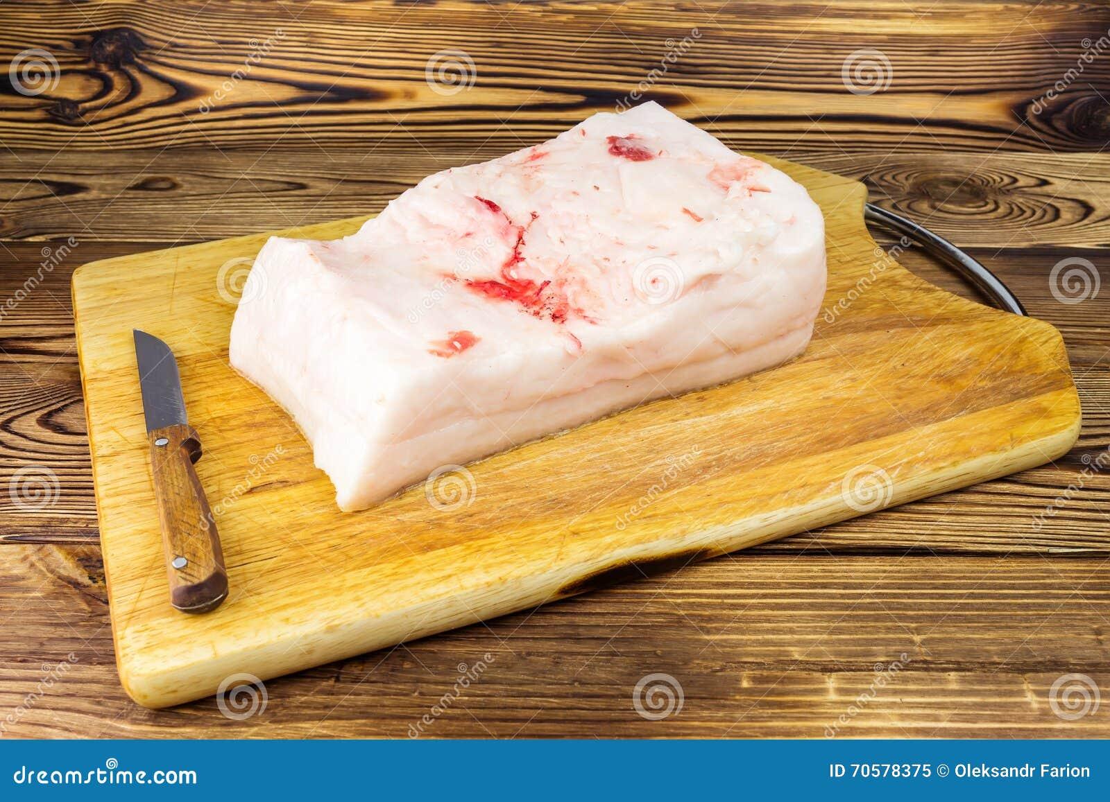 Stuk van vers, ruw varkensvleesreuzel en mes op houten raad, rustieke achtergrond