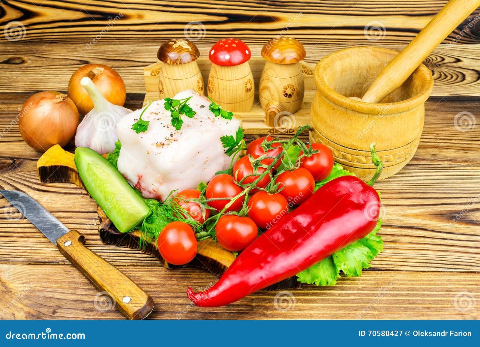 Stuk van verse varkensvleesreuzel, vers product, greens, groenten op de houten raad en mes op lijst