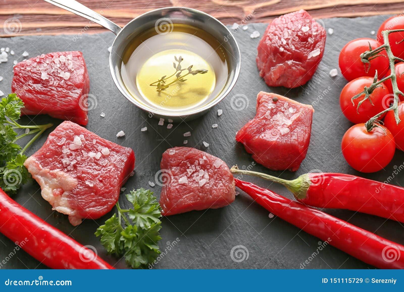 Stukken ruwe vlees, olijfolie en kruiden op lijst