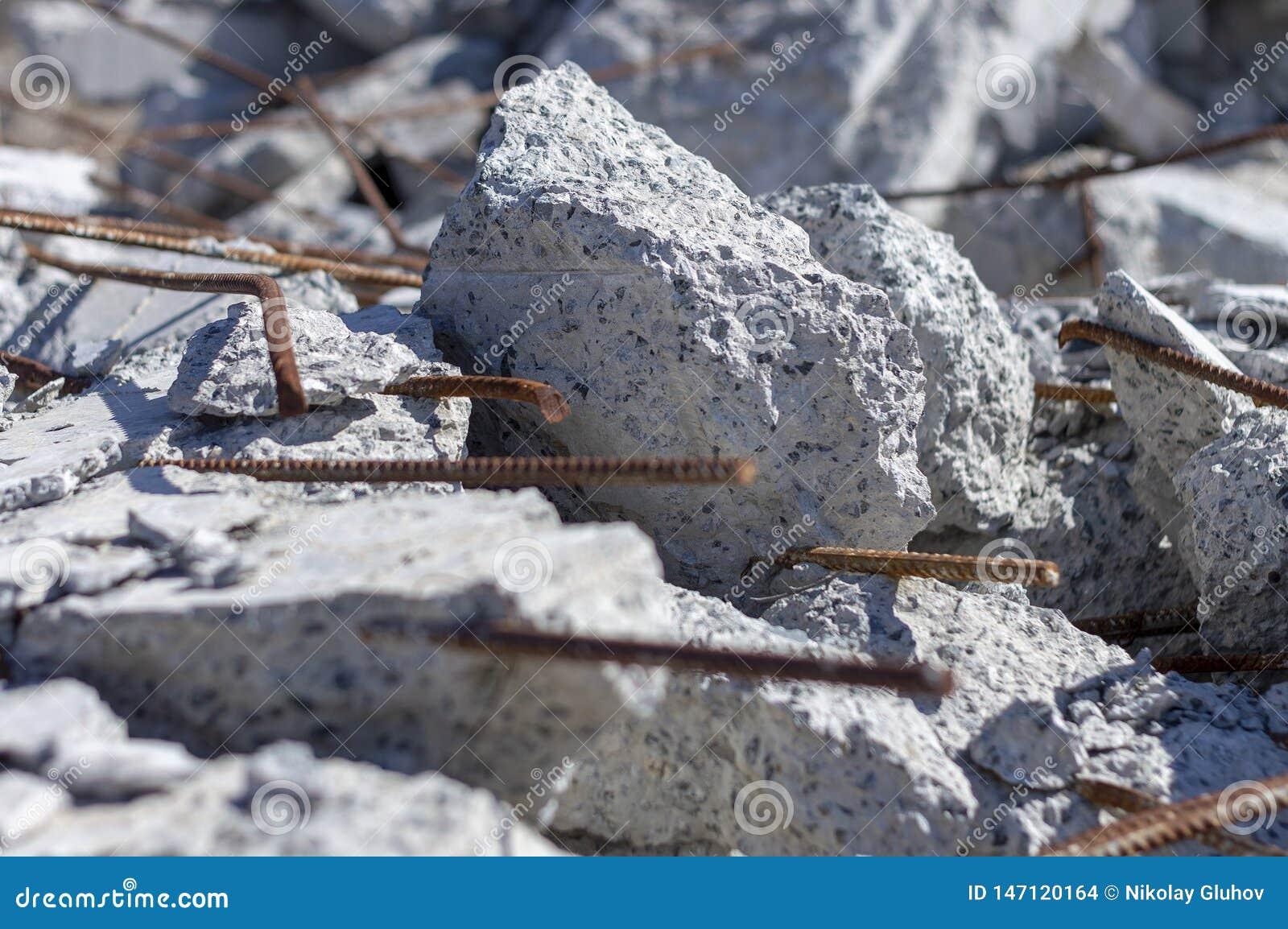 Stukken van beton en versterking na de vernietiging van het oude gebouw