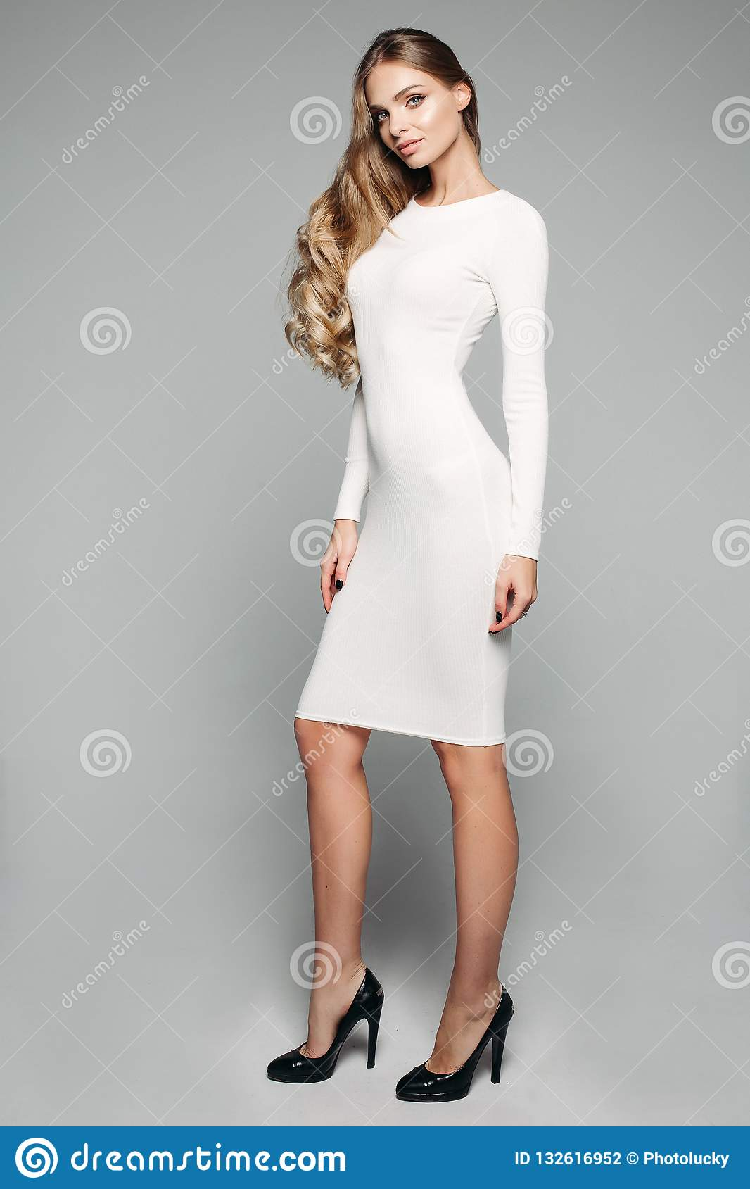 86d7bc7d6ea Stunning Blonde Girl In White Simple Dress And Black Heels. Stock ...