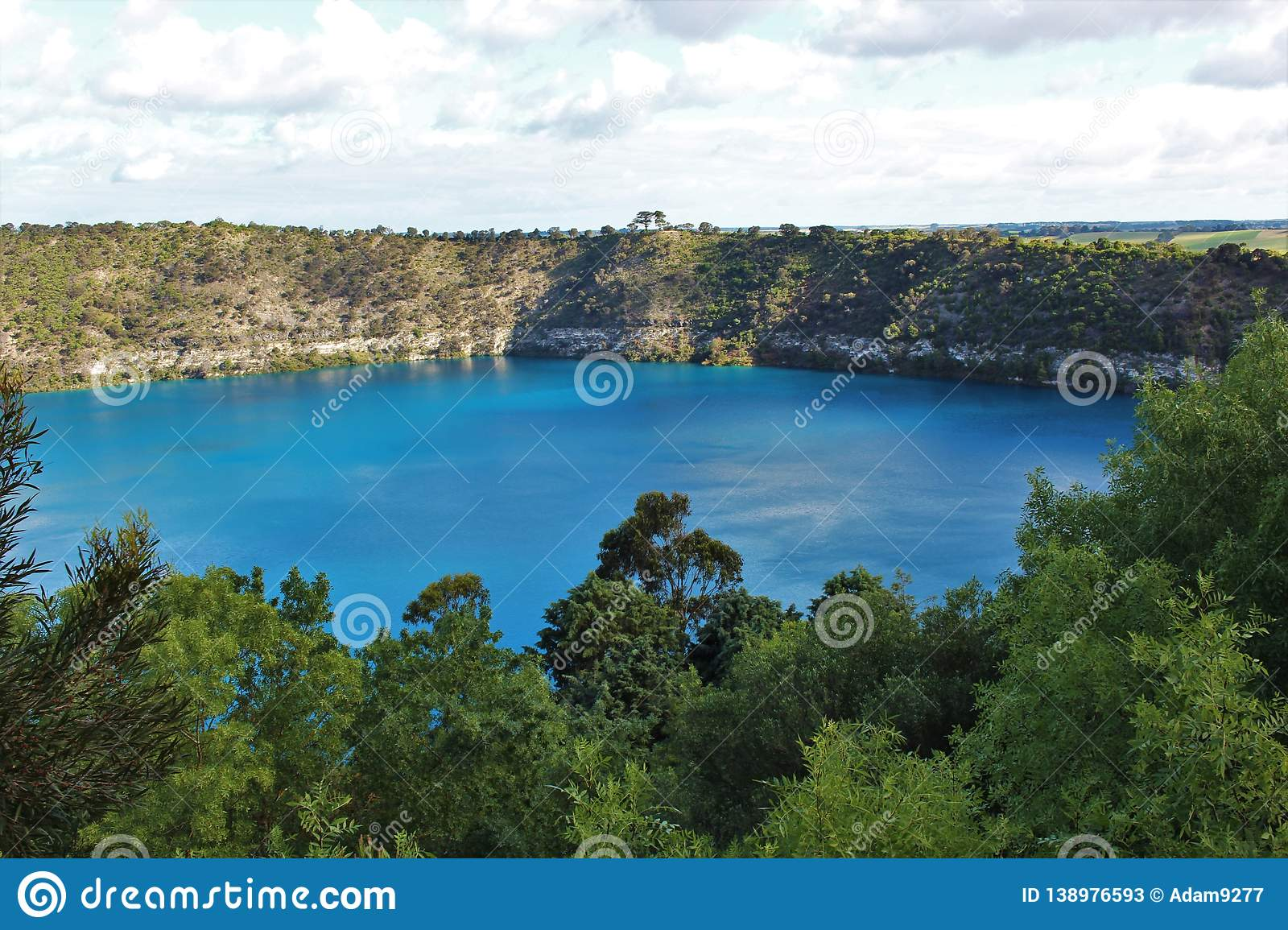 Stunning blue lake at Mount Gambier, Australia. Beautiful natural blue lake in a crater at Mount Gambier, Australia. Lake surrounded by cliffs with trees and stock photos