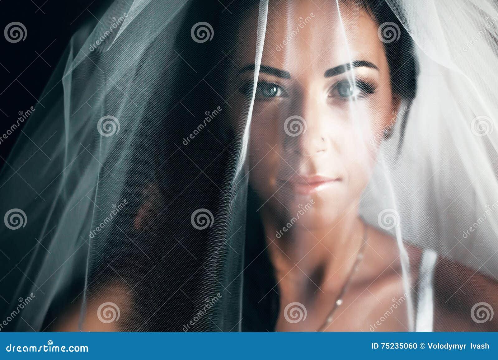 Stunning bride with black hair looks hidden under a veil
