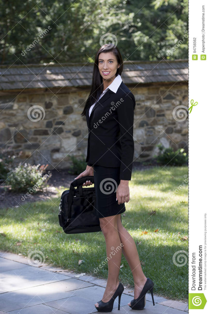 ec04807203e Beautiful brunette business woman wearing black skirt suit and heels stands  in courtyard holding briefcase