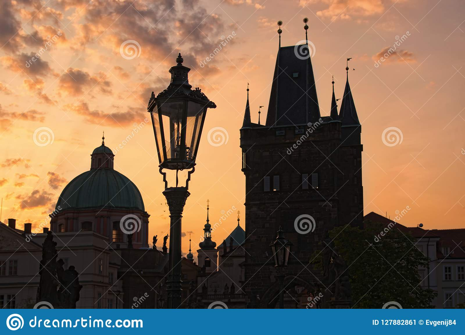 Stunning cityscape of Charles Bridge during sunrise. Statues on Charles Bridge, lanterns and Old Town Bridge Tower.