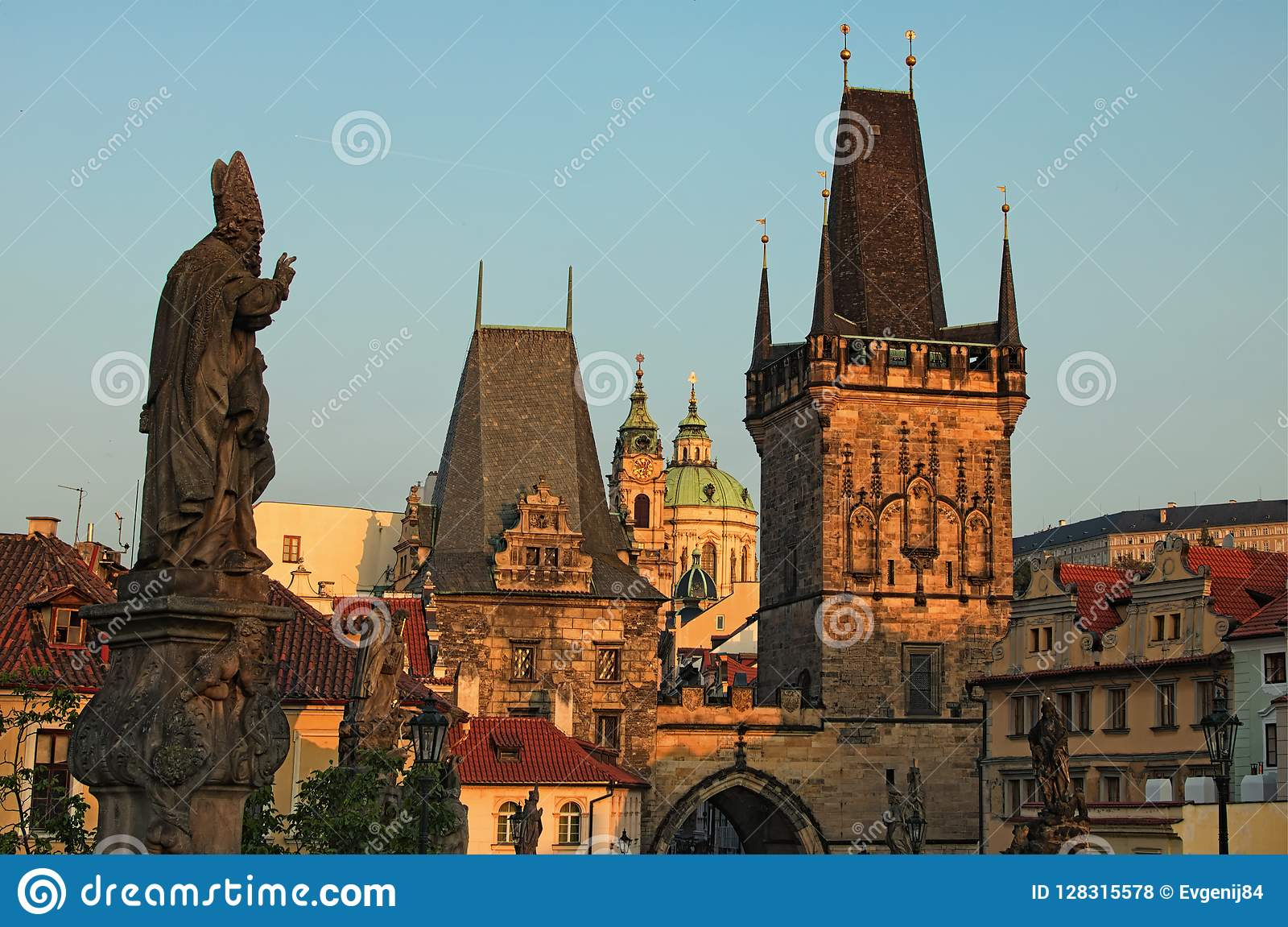 Stunning cityscape of Charles Bridge during sunrise. Statues on Charles Bridge, lanterns and Old Town Bridge Tower