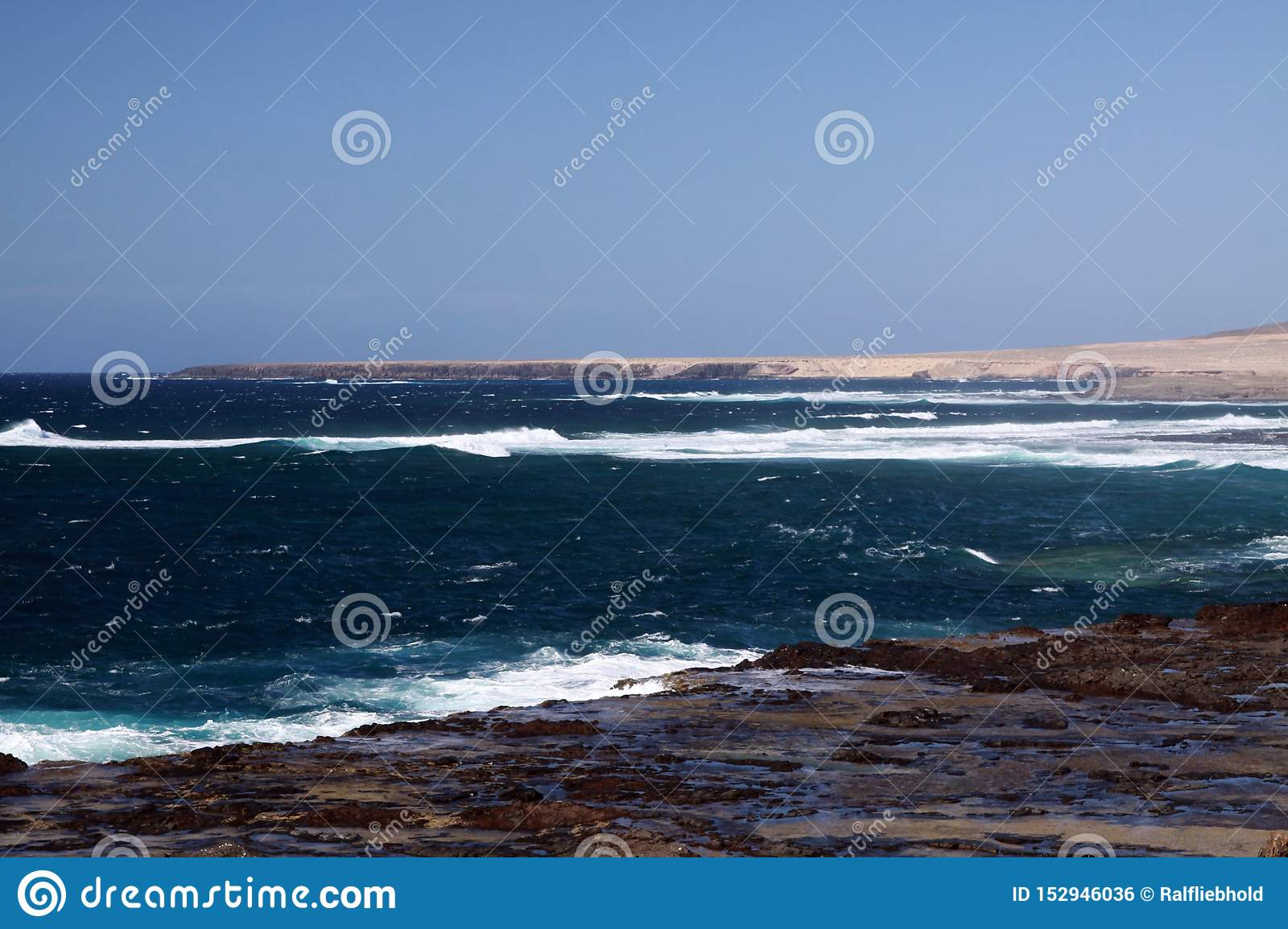 Stunning natural viewpoint with bare dry hills, turquoise lagoon and furious wild sea at north-west coast of Fuerteventura, Canary
