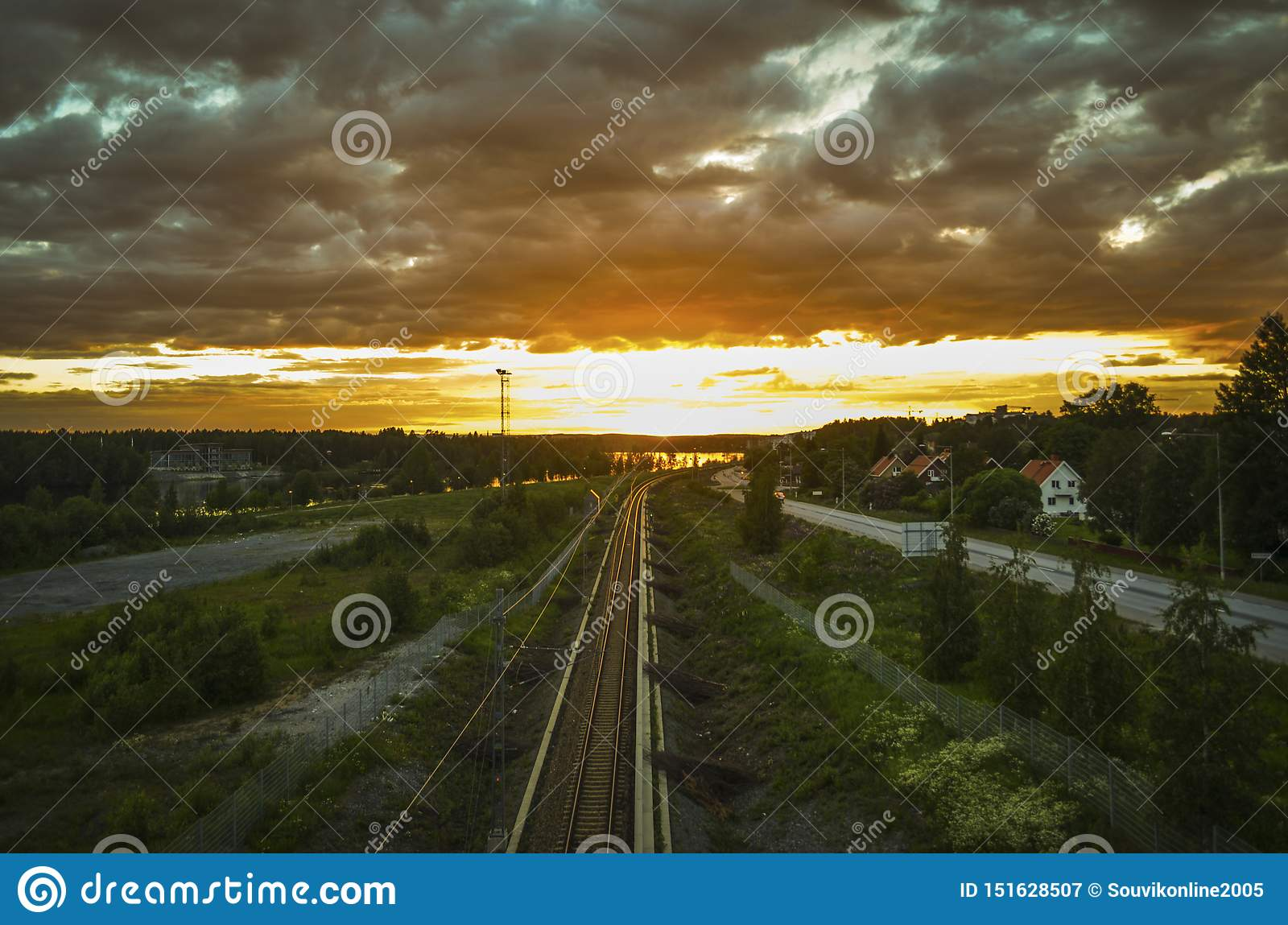 Stunning reflection of sunlight on moving cloud and leading train line to the orange horizon in beatiful summer day in a cityscape