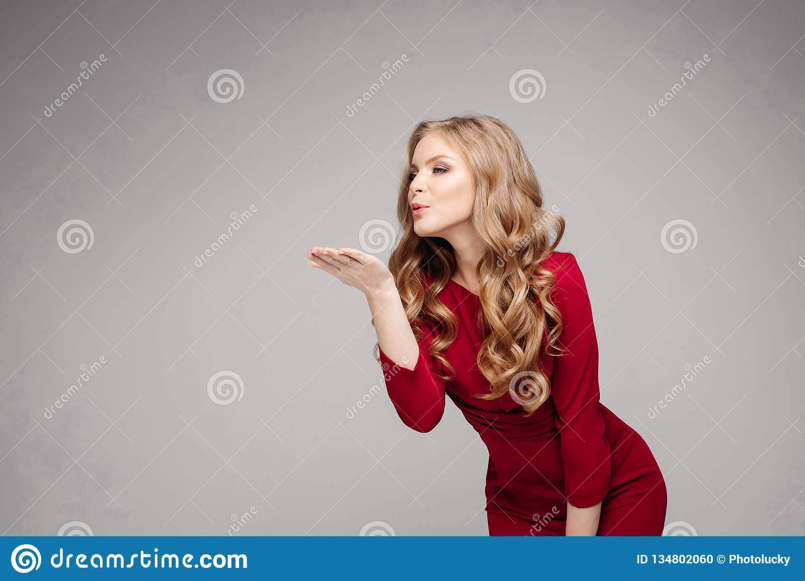 79ab8b507fa Studio portrait of attractive woman with long wavy hair in tail wearing  mini red dress and black high heels over white background. Isolate.