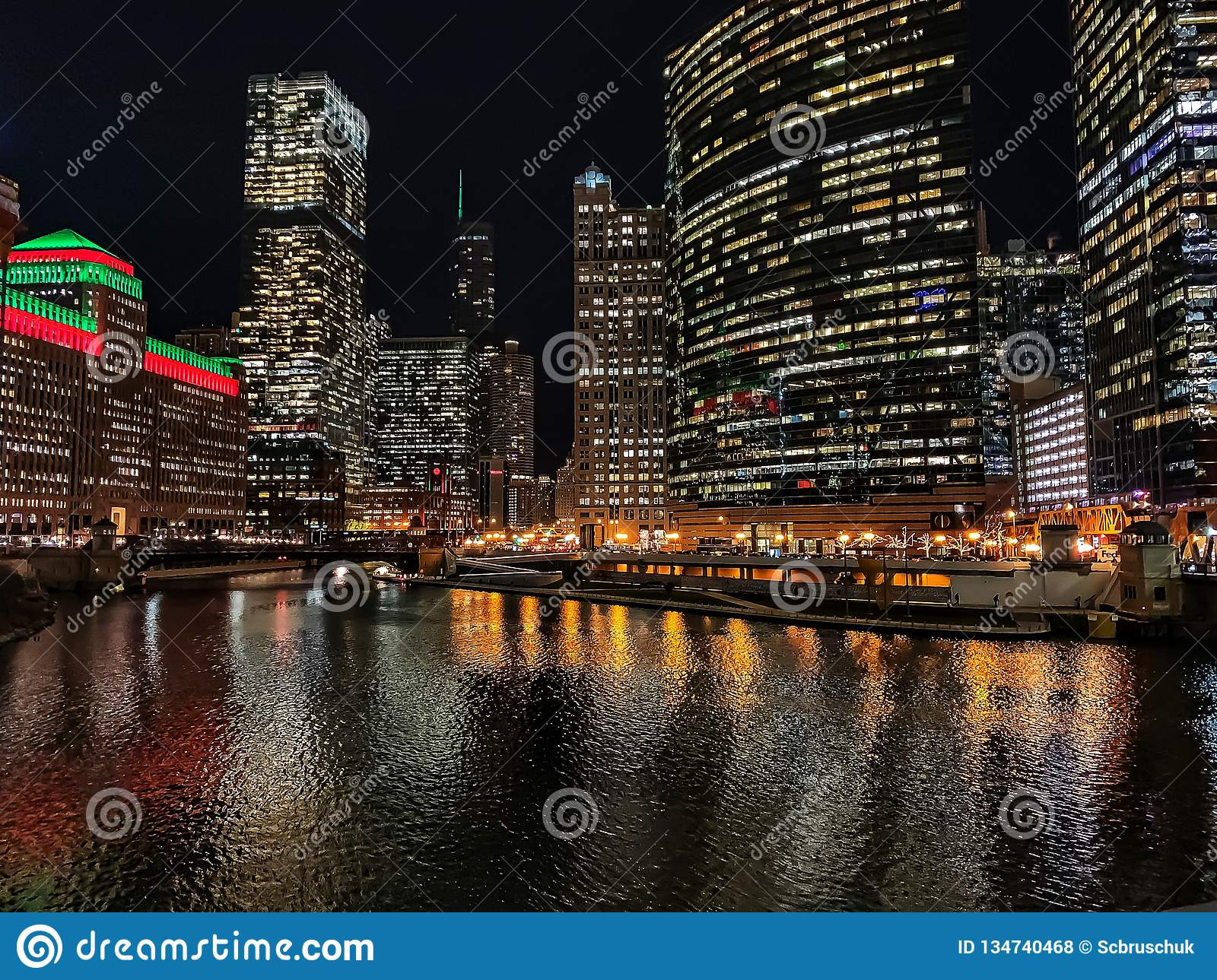 Stunning view of Chicago cityscape with holiday/Christmas colors illuminated over the water.