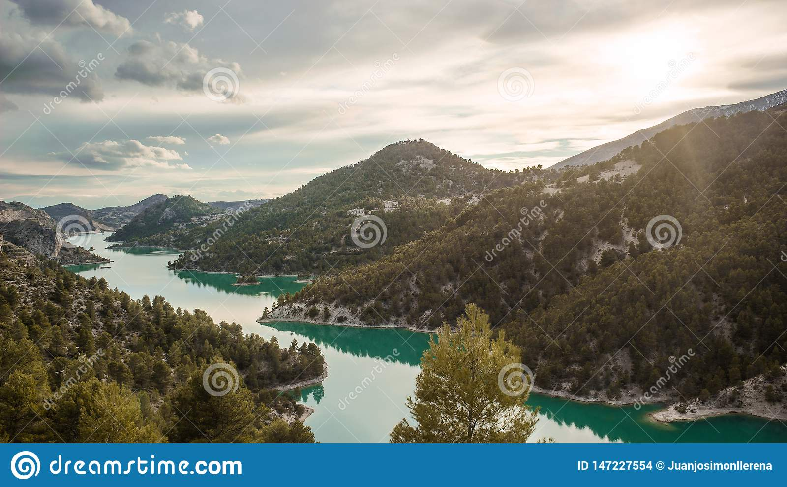 Stunning view of the lake El Portillo with the sun shinning above the mountains. Fantasy land
