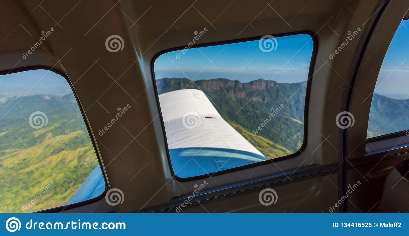 Stunning view of mountain range from a window of a small airplane during take off. Air travel in Fiji, Melanesia, Oceania.