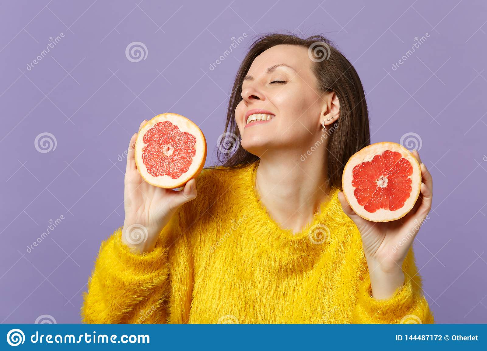 Stunning young woman in fur sweater keeping eyes closed holding halfs of fresh ripe grapefruit isolated on violet pastel