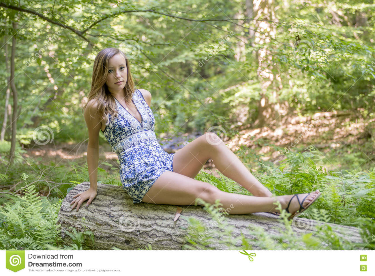 8d7ce51da9 Beautiful young Caucasian woman wearing blue and white romper poses in woods