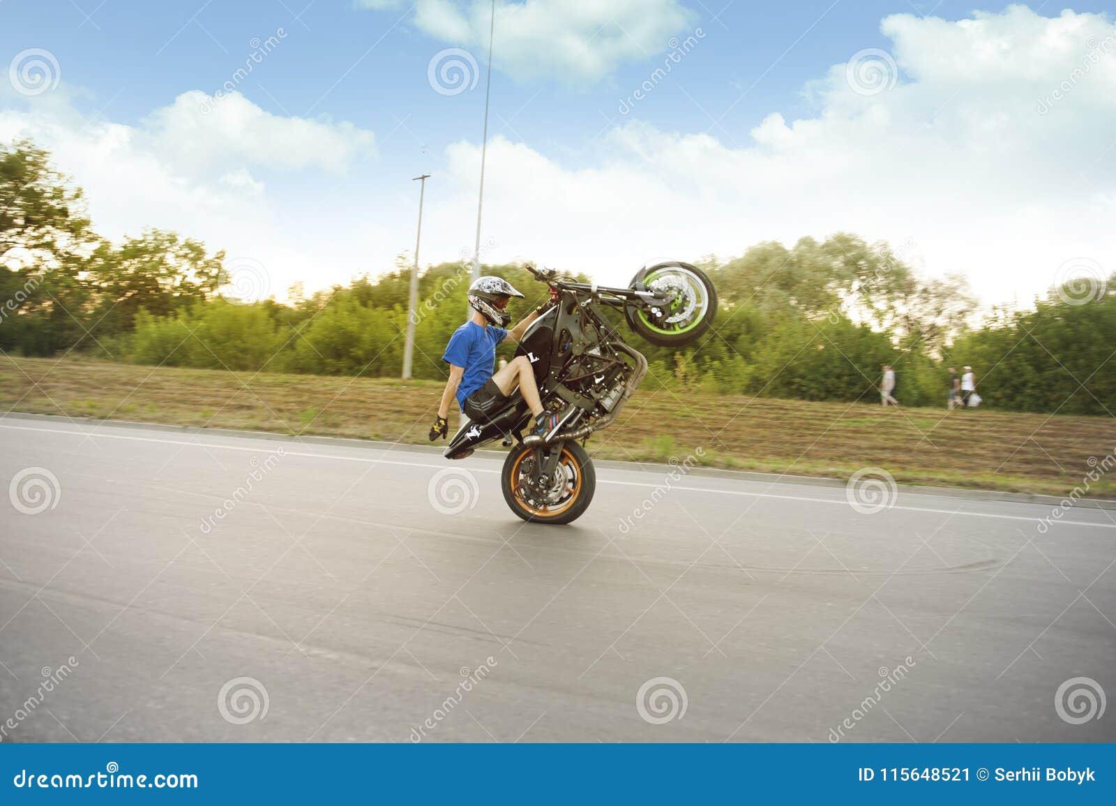 Stuntsman Riding Fast On One Wheel  Editorial Photo - Image of ride