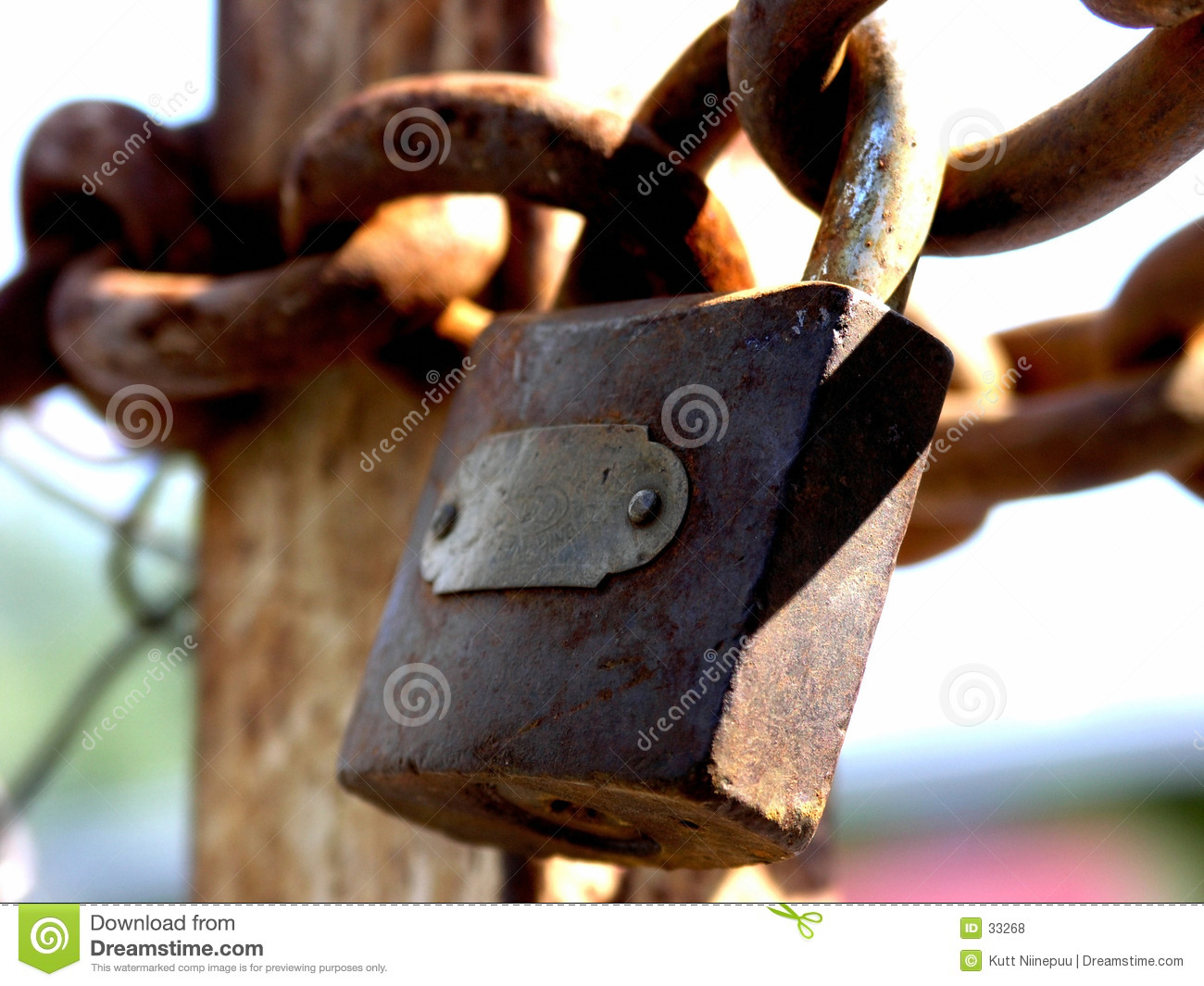 Closeup of closed gates with a rusty padlock and thick chains at a ...