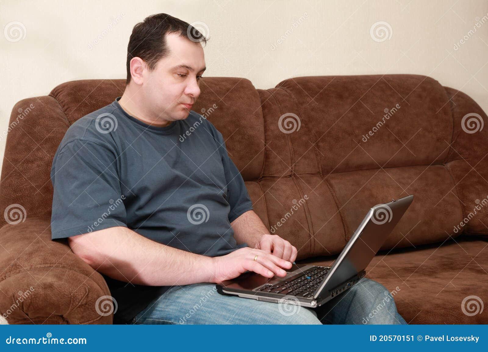 Stwarzać ognisko domowe laptopu mężczyzna siedzącego kanapy działanie