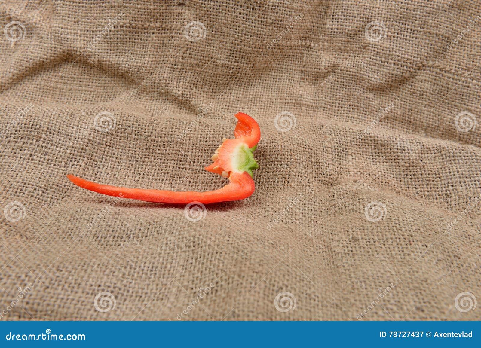 Stycke av röd peppar som ligger på på säckvävbakgrund Begrepp av