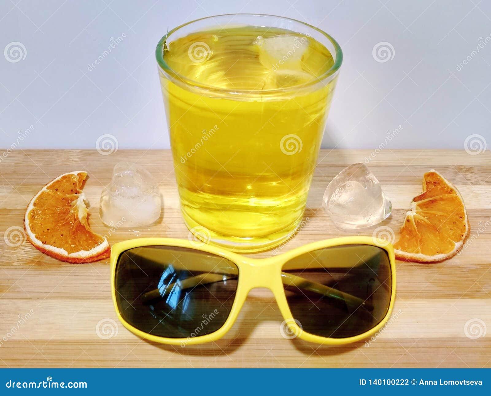 Stycken av isflötet i ett exponeringsglas av fruktsaft