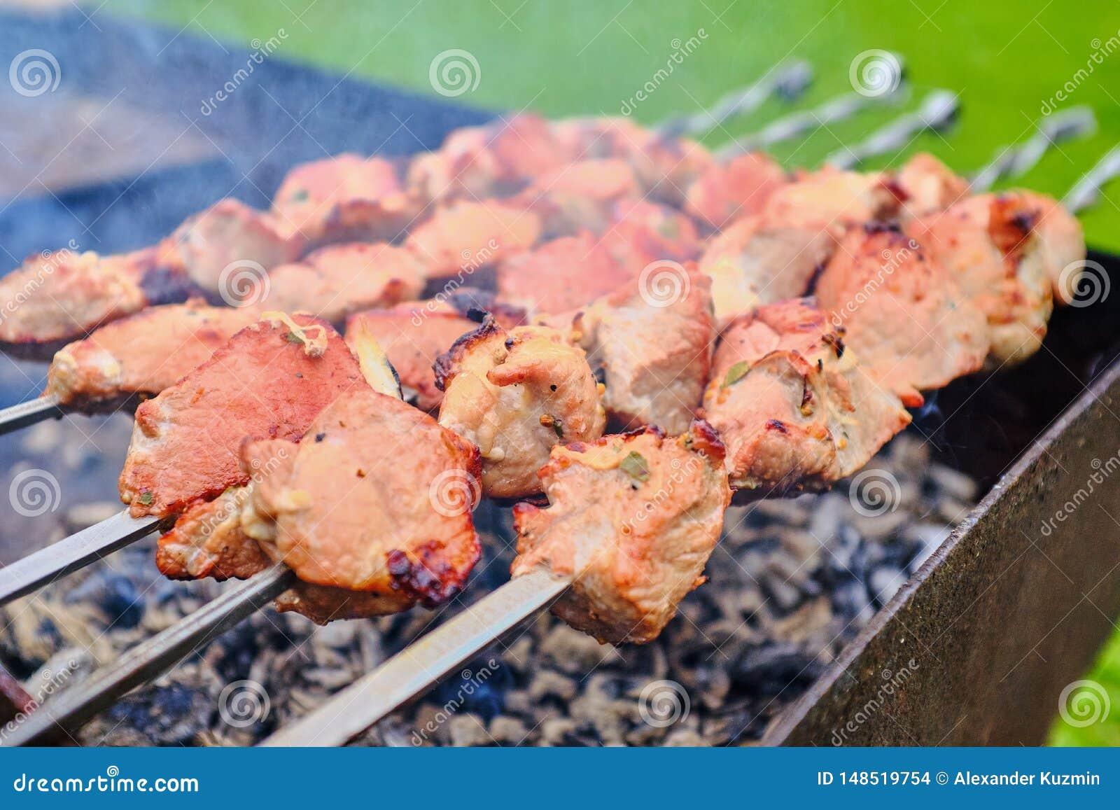 Stycken av kött stekas på brand på steknålar