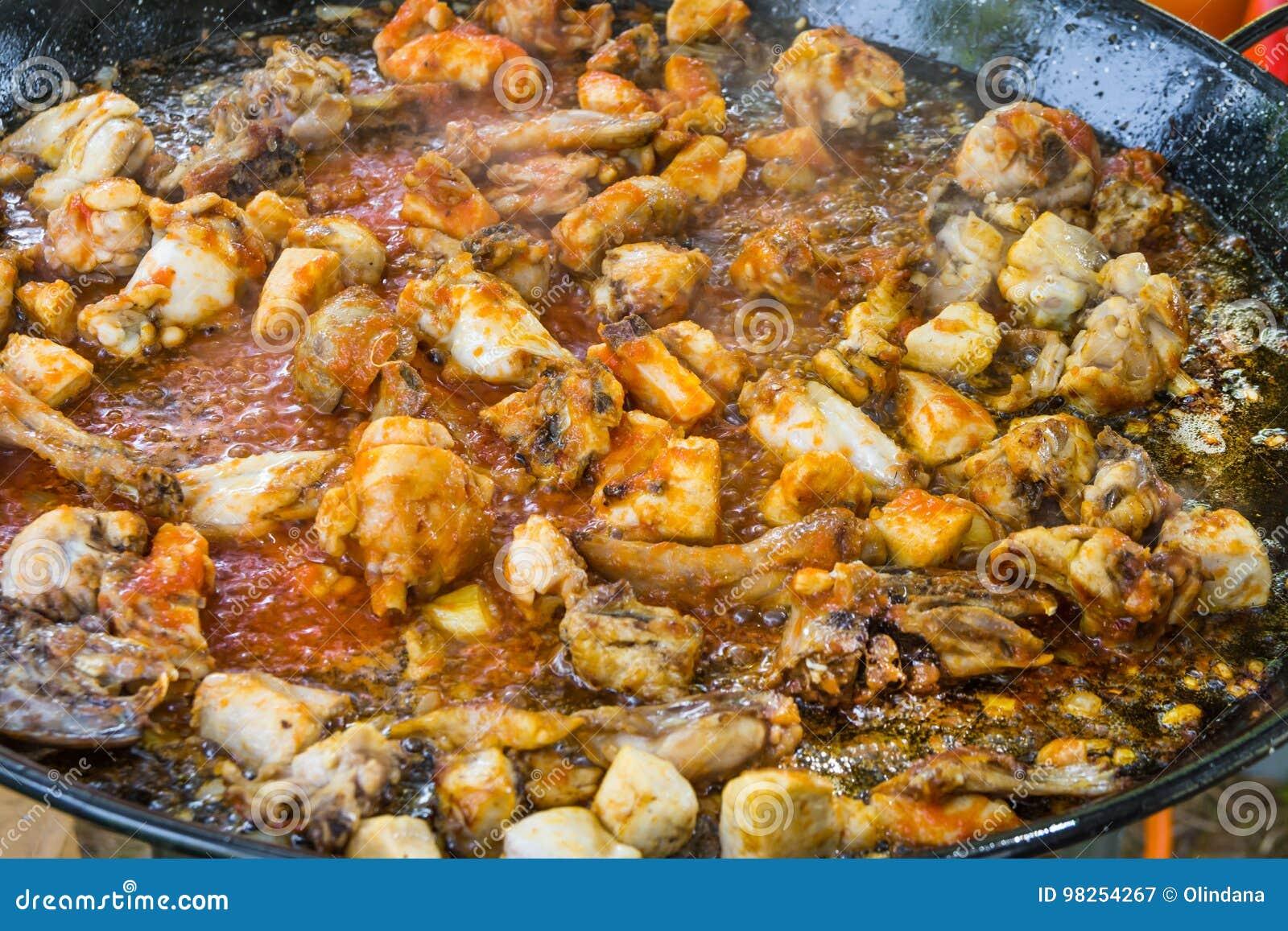 Stycken av kanin- och hönakött som steker med tomatsås i olivolja i stor plan panna Matlagningpaella eller jambalaya