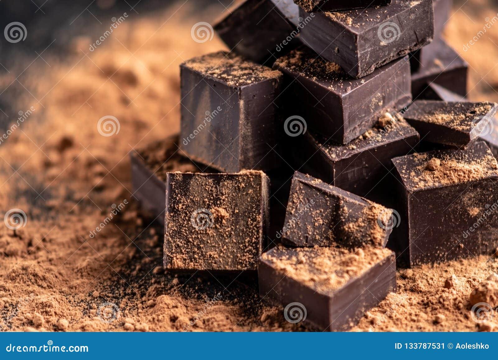 Stycken av mörk bitter choklad med kakaopulver på mörk träbakgrund Begrepp av konfektingredienser