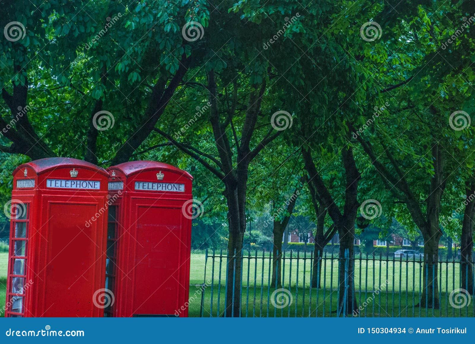 Style de cru des cabines téléphoniques rouges typiques sur la rue pluvieuse à Londres