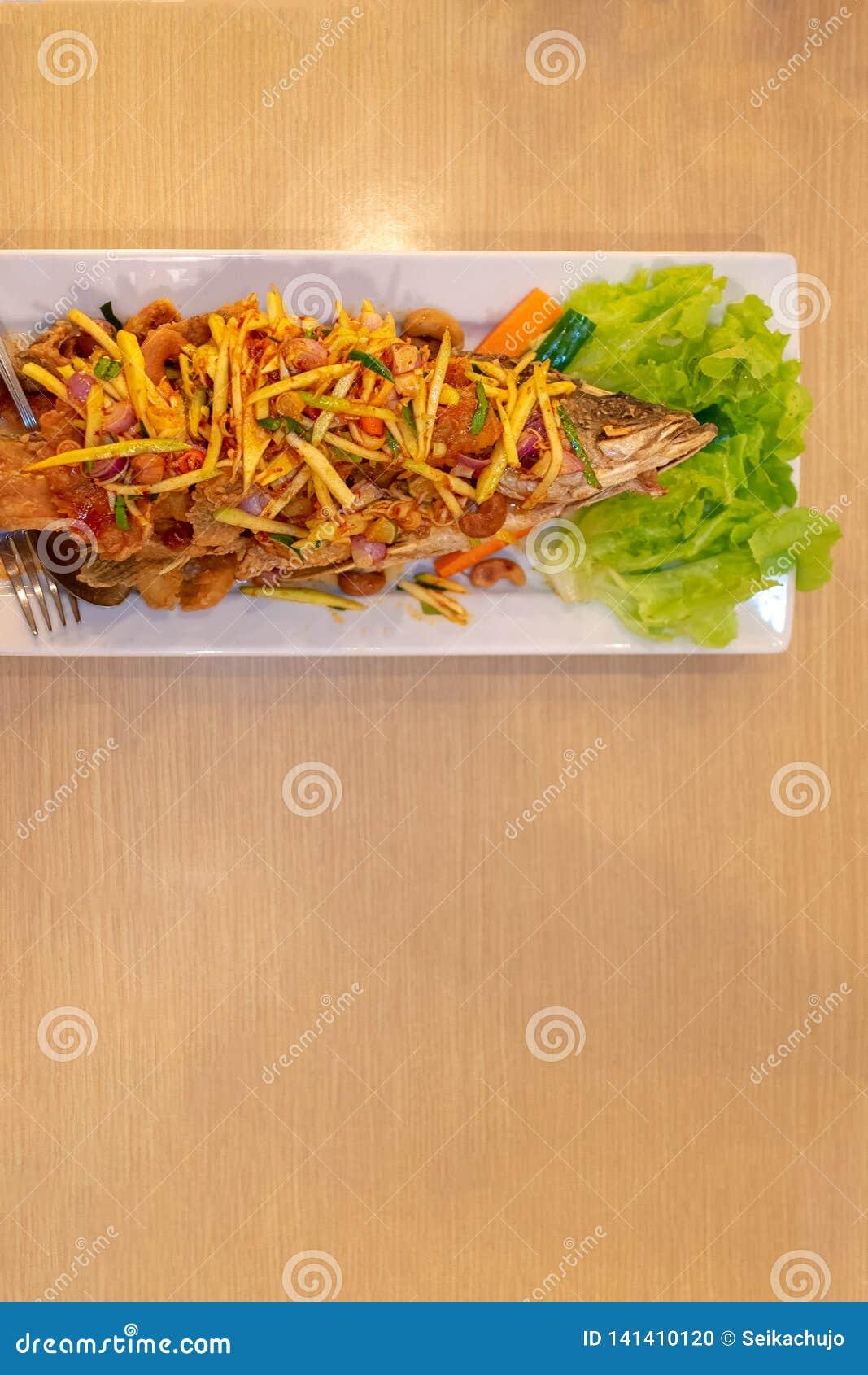 Style thaïlandais Fried Fish profond avec de la salade de mangue sur le dessus